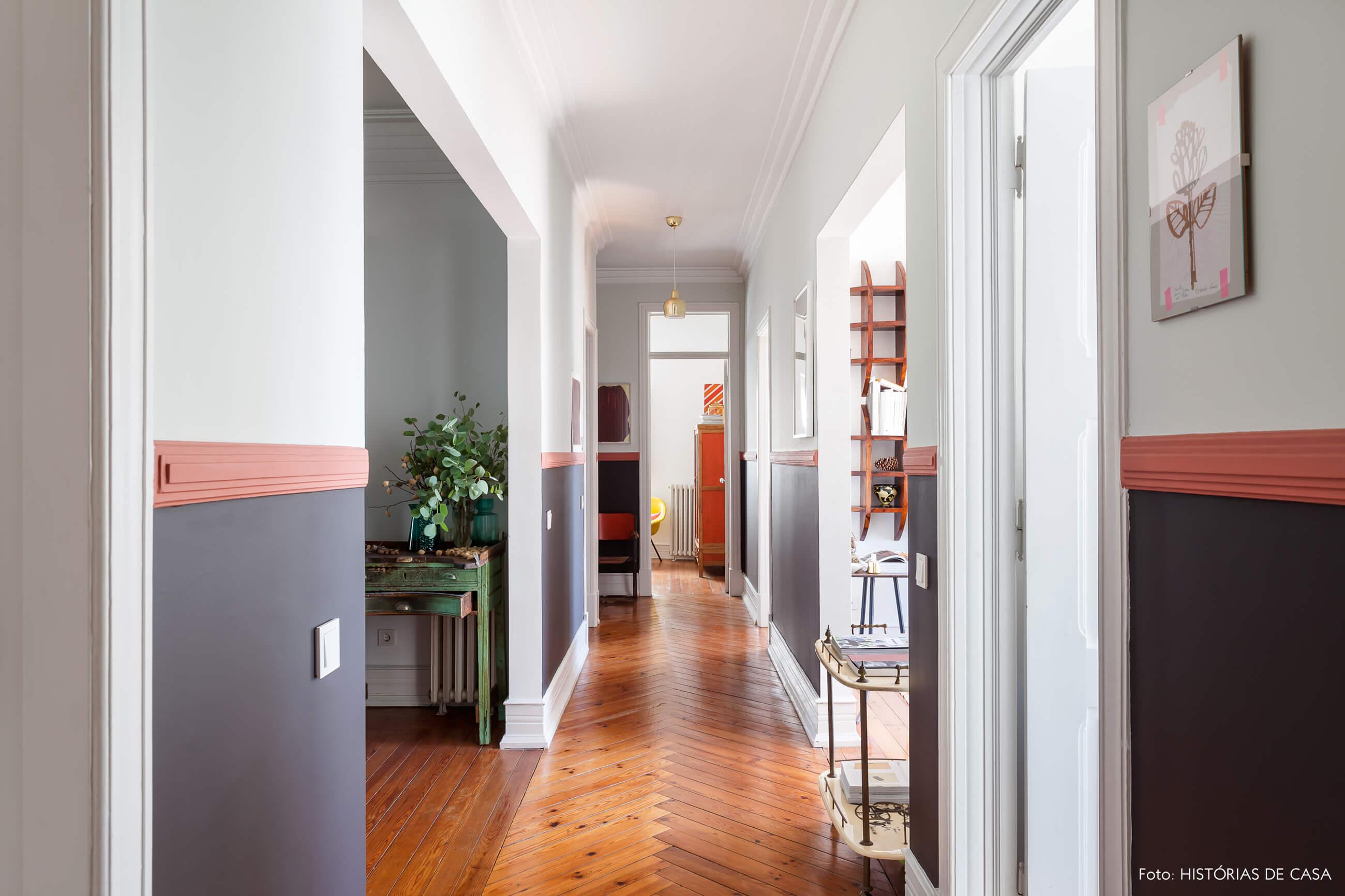 Decoração corredor meia parede preta e piso de madeira