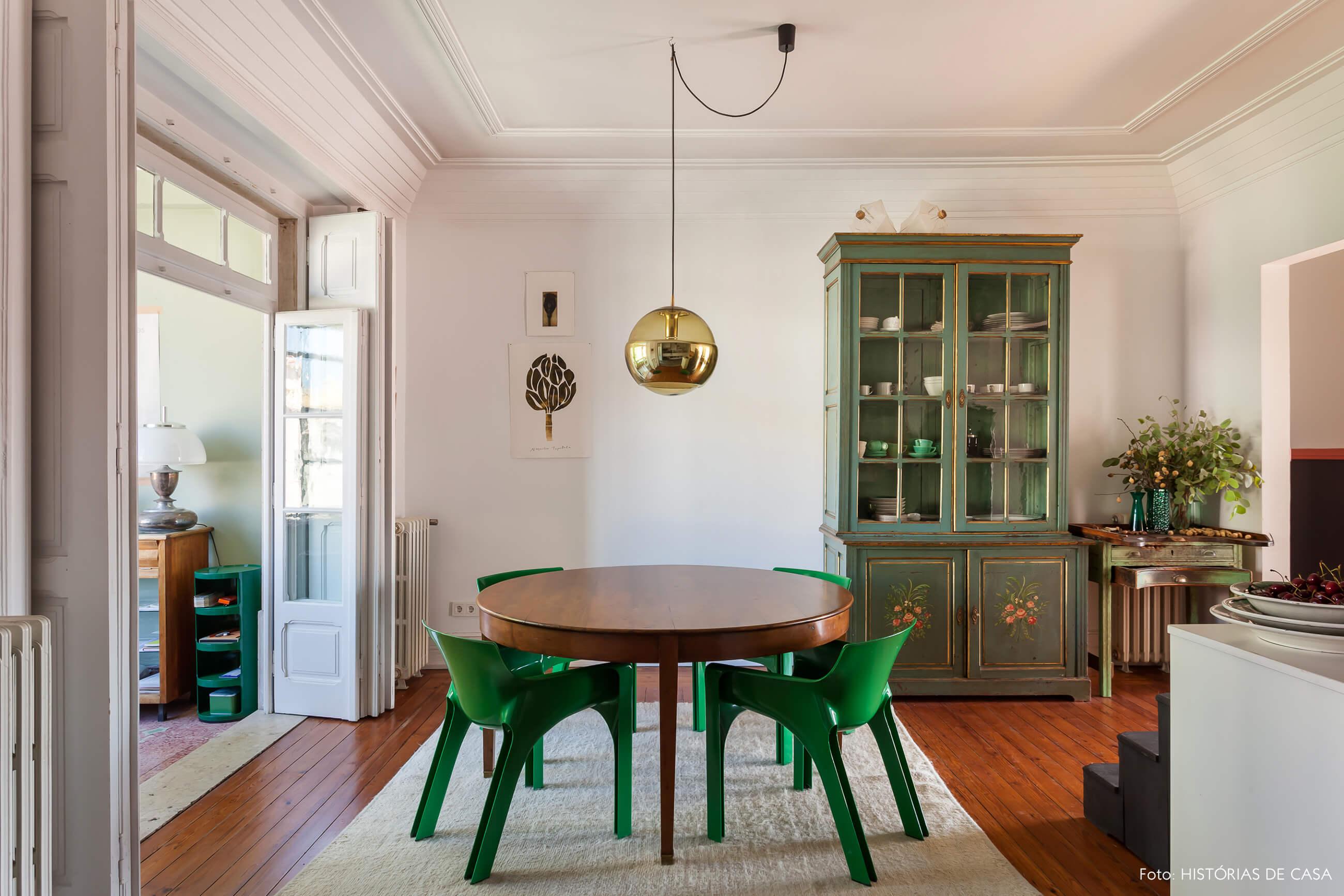 Decoração com cadeiras verdes e armário verde e luminária dourada