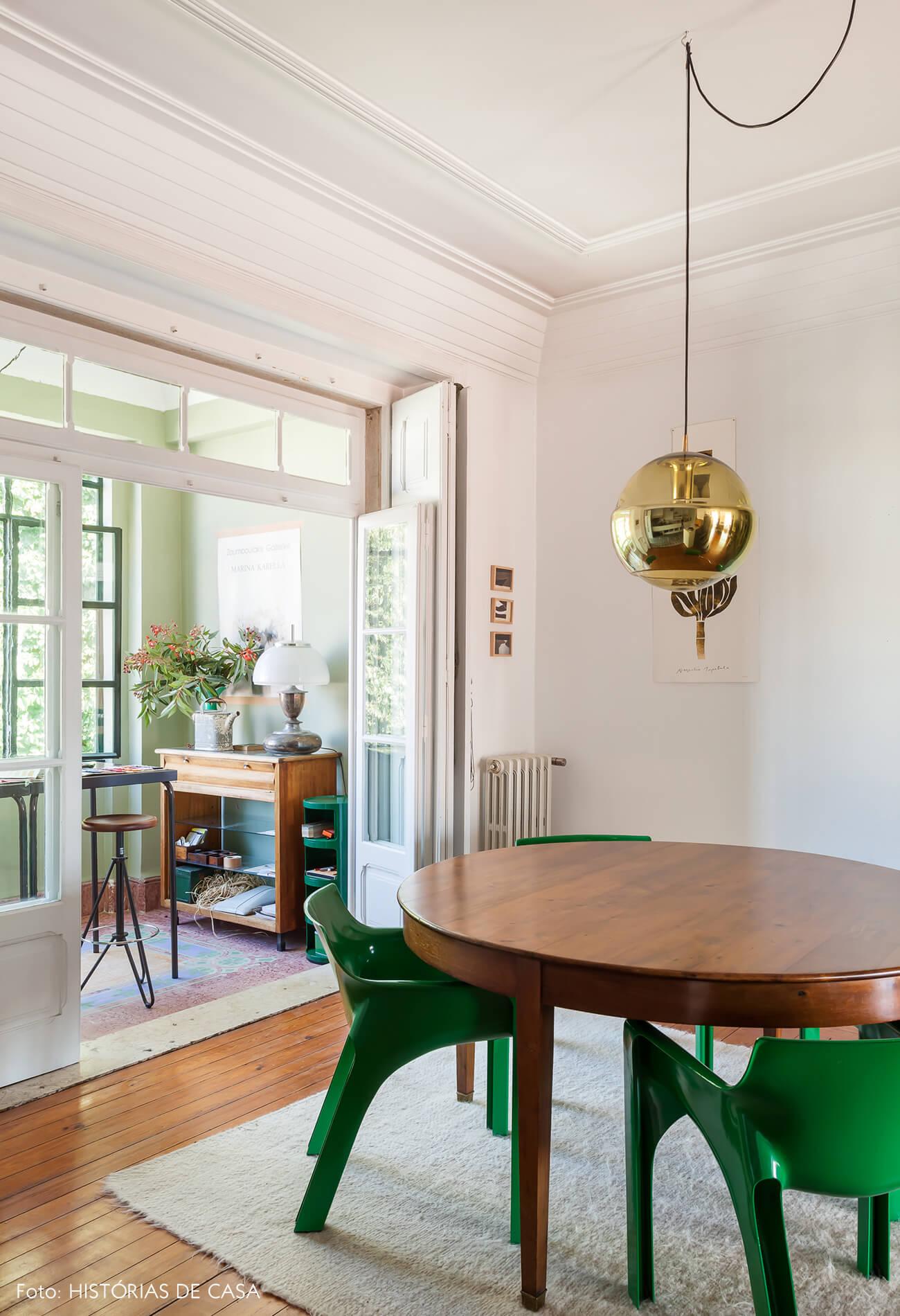 Decoração com piso e mesa de madeira cadeiras verdes luminária dourada e sacada