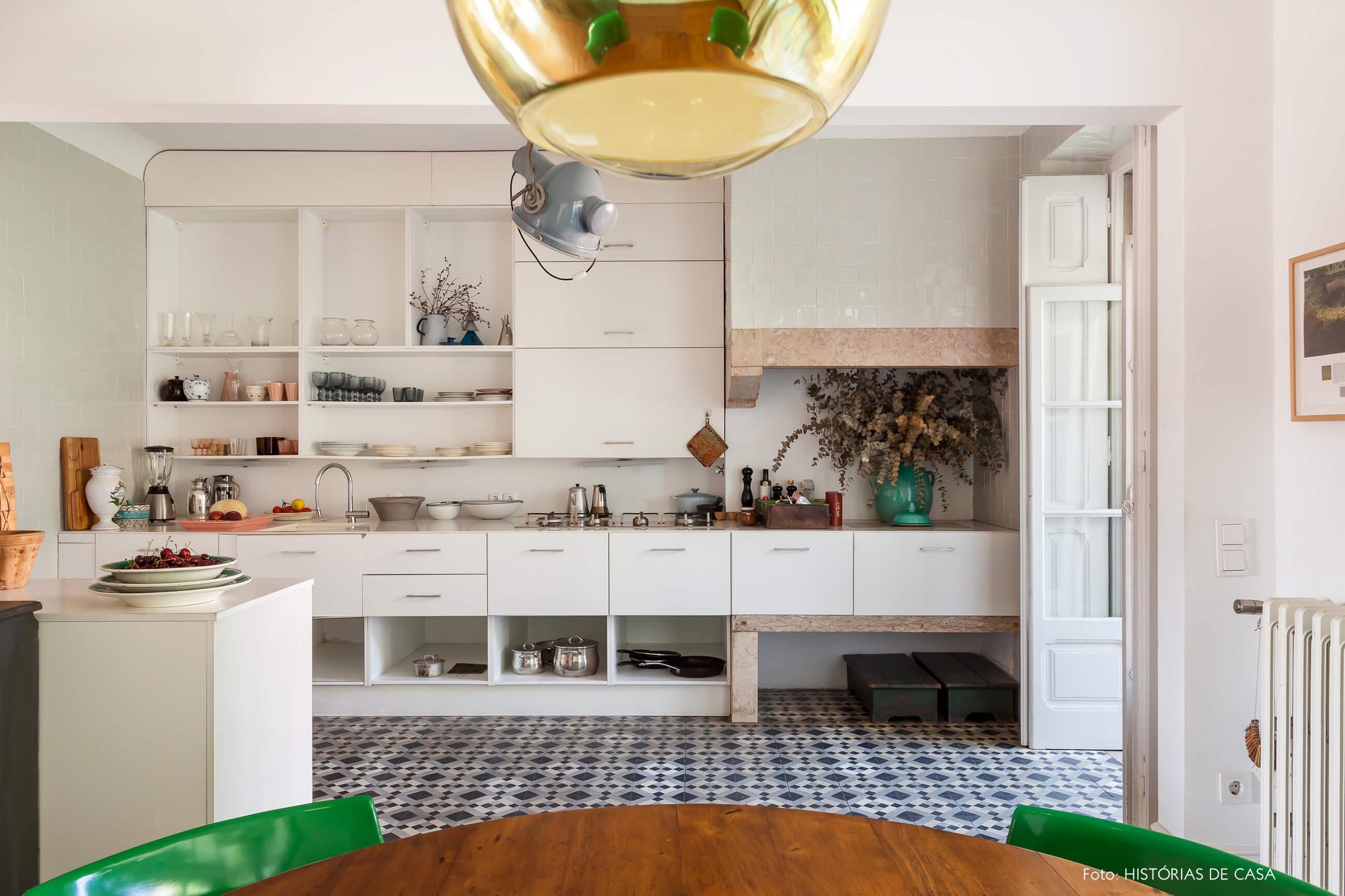 decoração da cozinha com caderias verdes luminária dourada e armários brancos