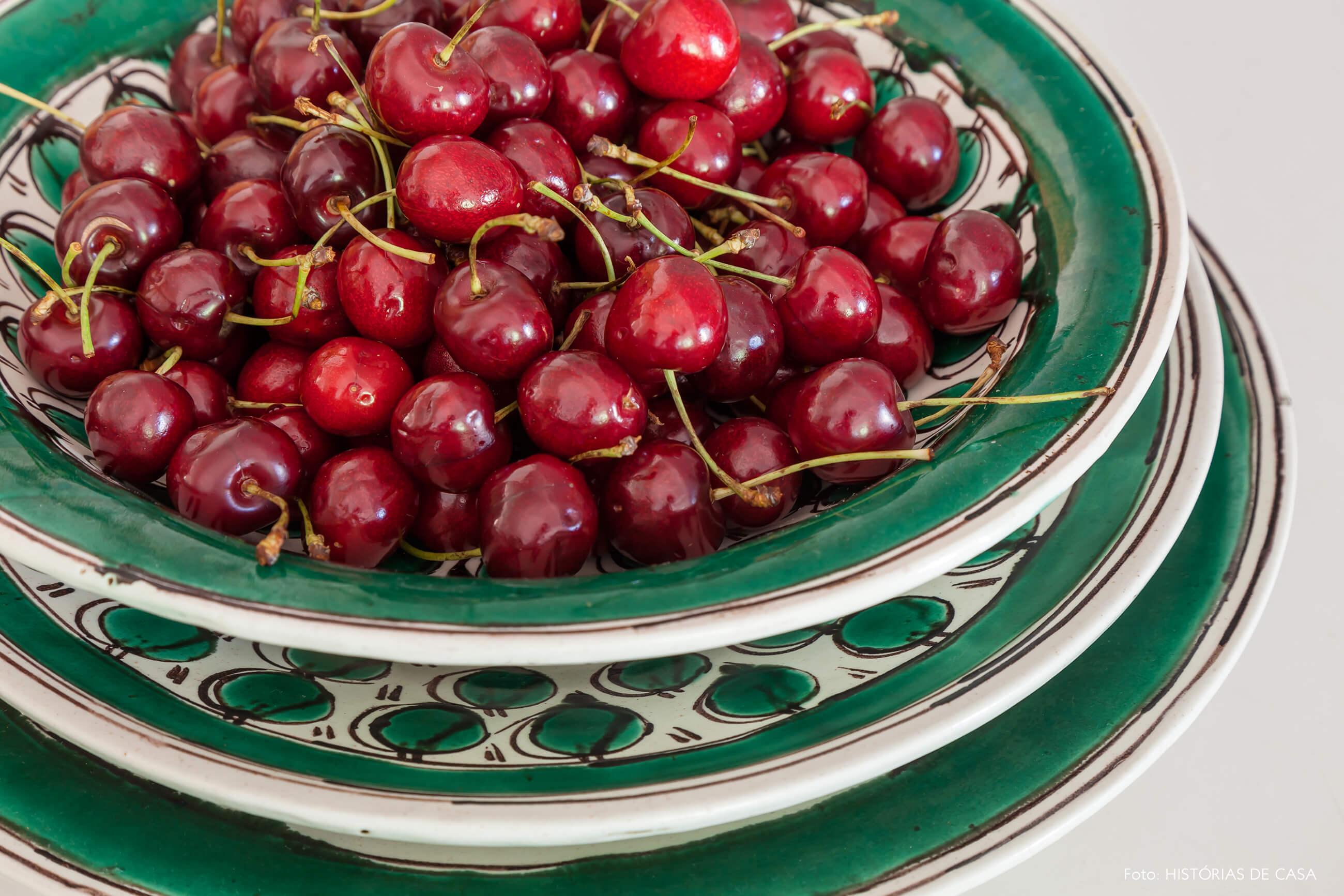 detalhe da decoração de prato verde e cerejas