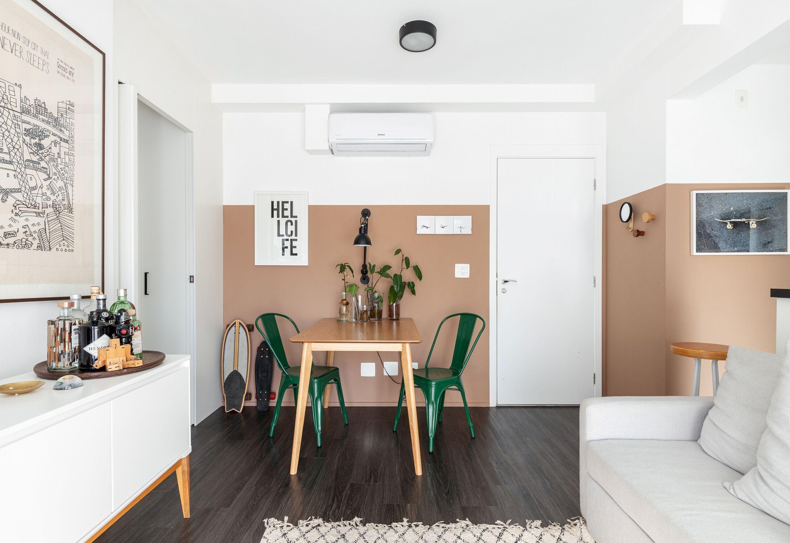 Sala com piso de madeira e parede rosa bege com mesa de madeira clara e cadeiras verdes e sofá cinza