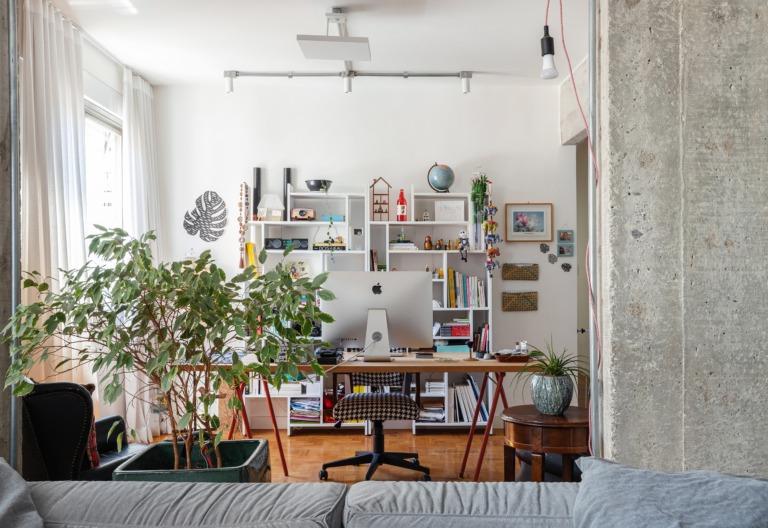 Sala e escritório com parede de concreto e plantas