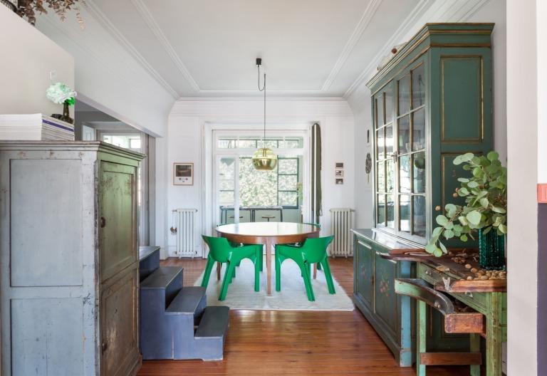 Sala decoração com piso de madeira e cadeiras e armários verdes