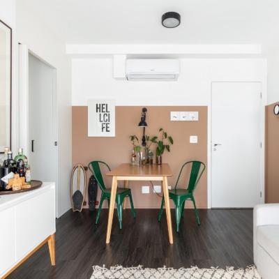 Sala com parede rosa bege e piso de madeira escura cadeiras verdes
