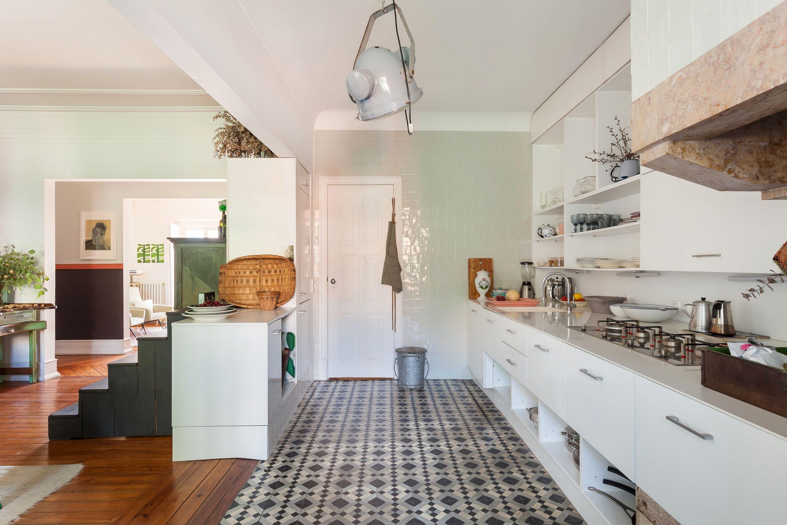 Cozinha com piso azulejo azul e sala com paredes verdes e luminaria azul