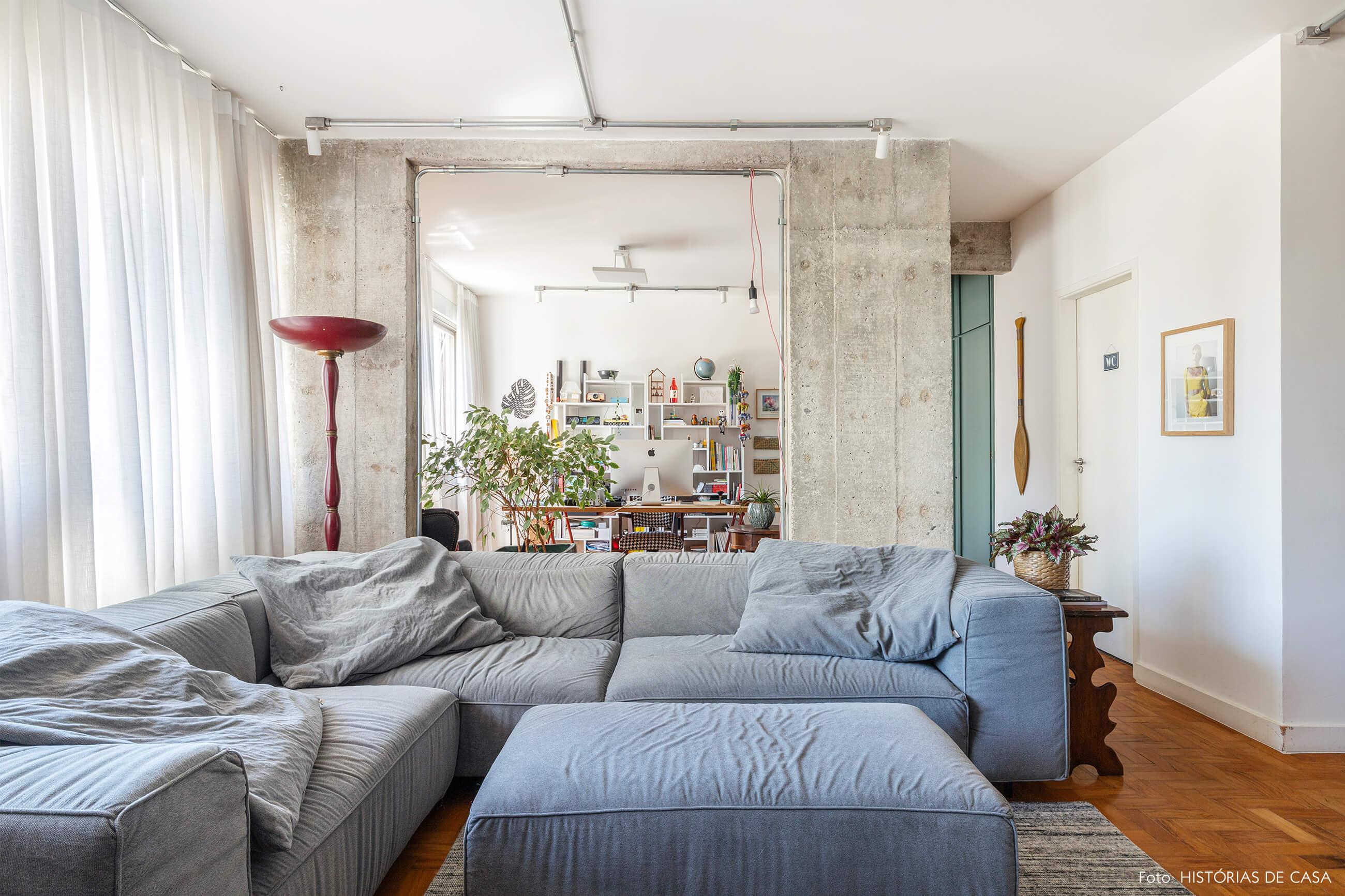 Sala com sofá azul e parede de concreto