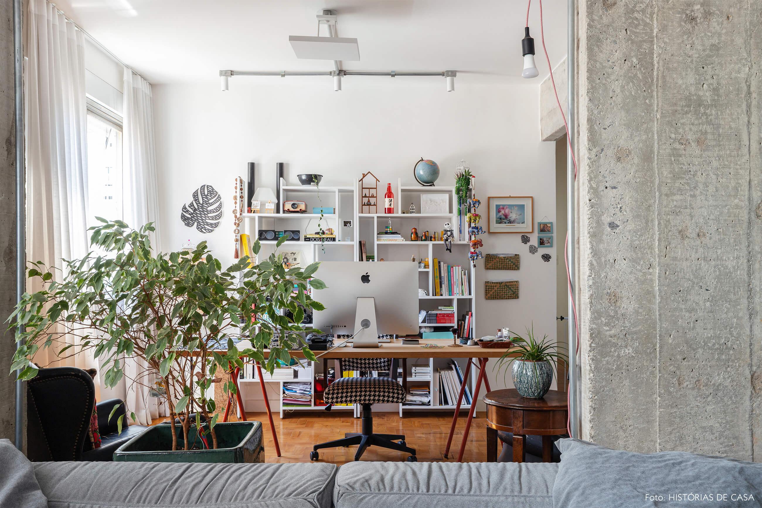 Escritório com parede de concreto e planta