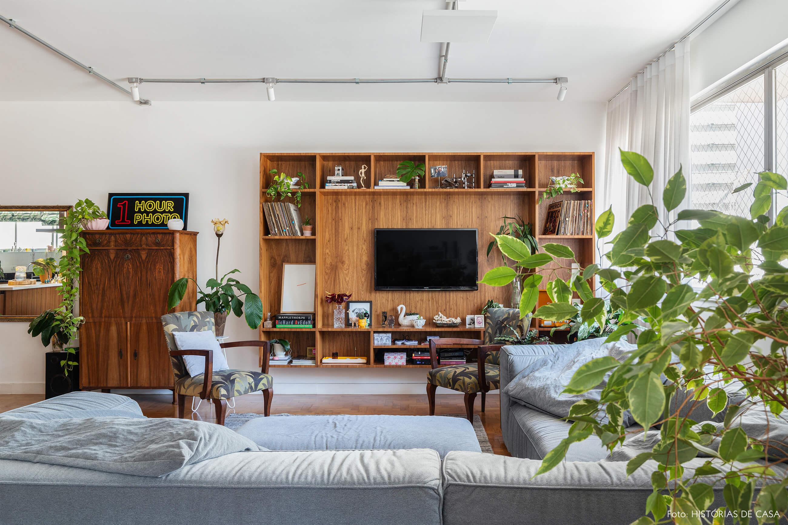 Sala TV com sofá azul estante de madeira e plantas