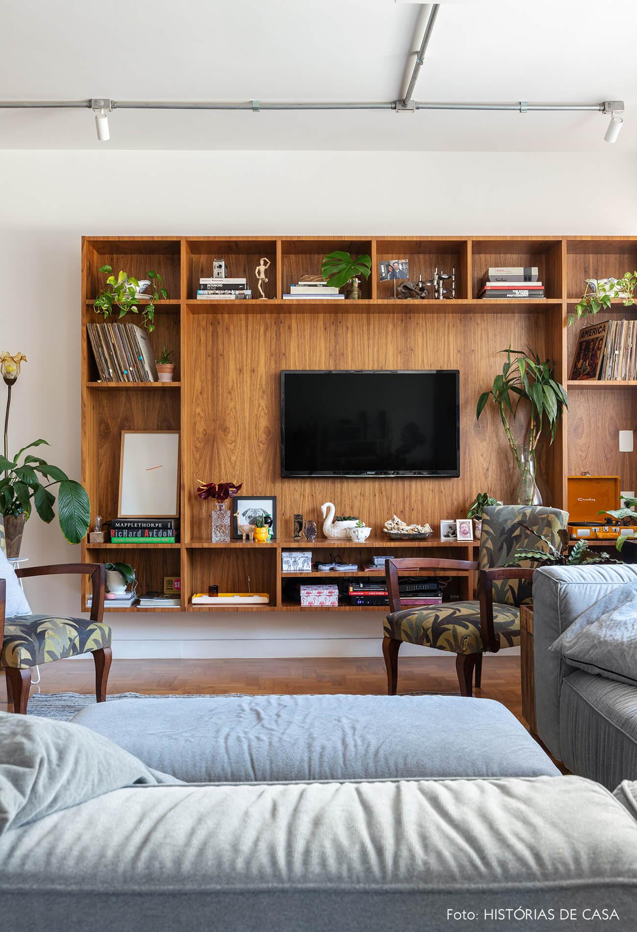 Sala TV com sofá azul e estante madeira