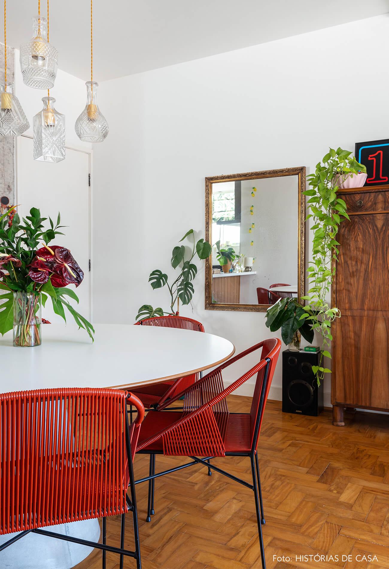 Sala jantar chão de madeira com cadeira vermelha e plantas