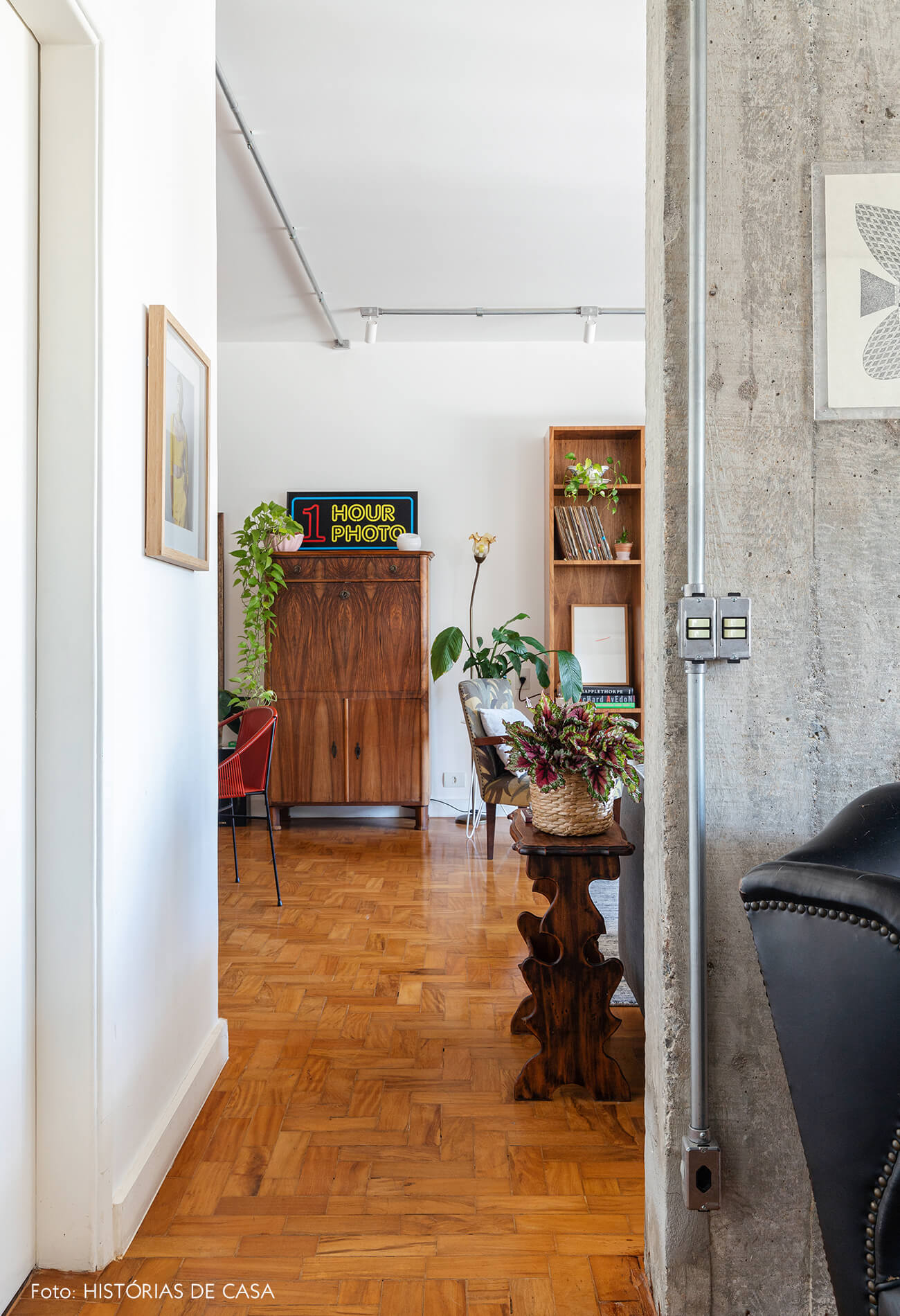 Sala com parede de concreto e chão de madeira