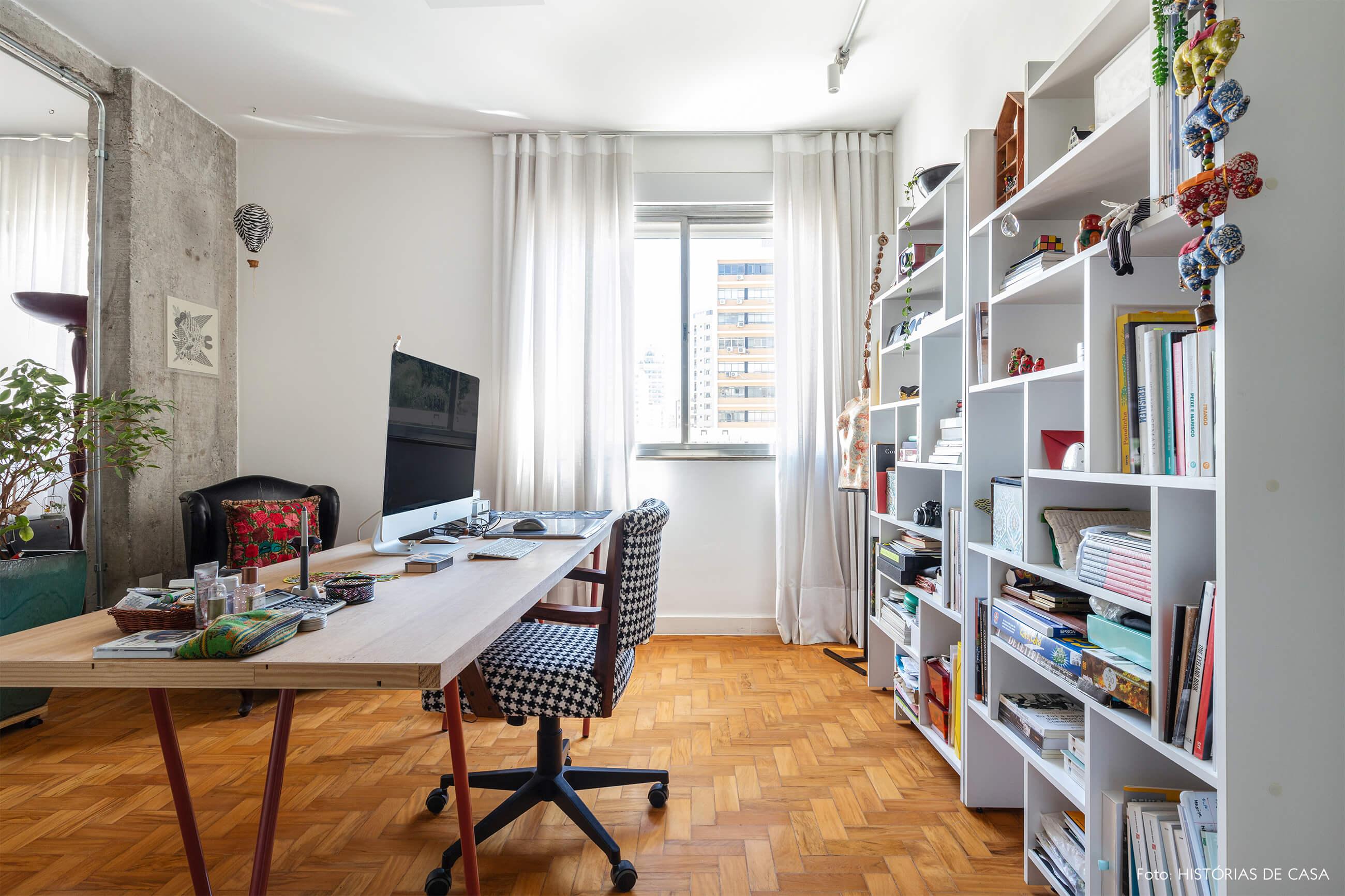 Escritório com piso de madeira e paredes brancas