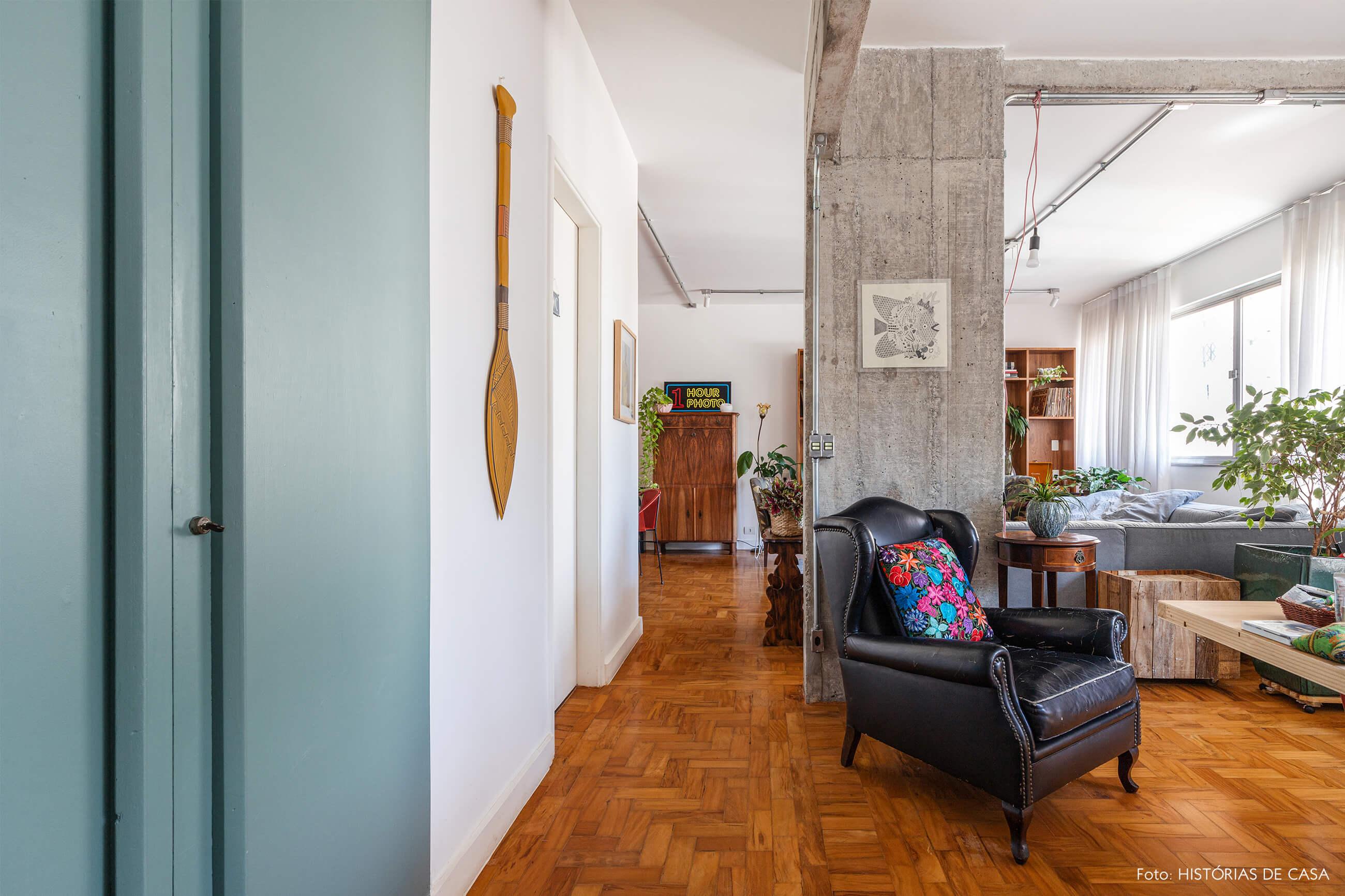 Sala com piso de madeira parede de concreto e poltrona de couro