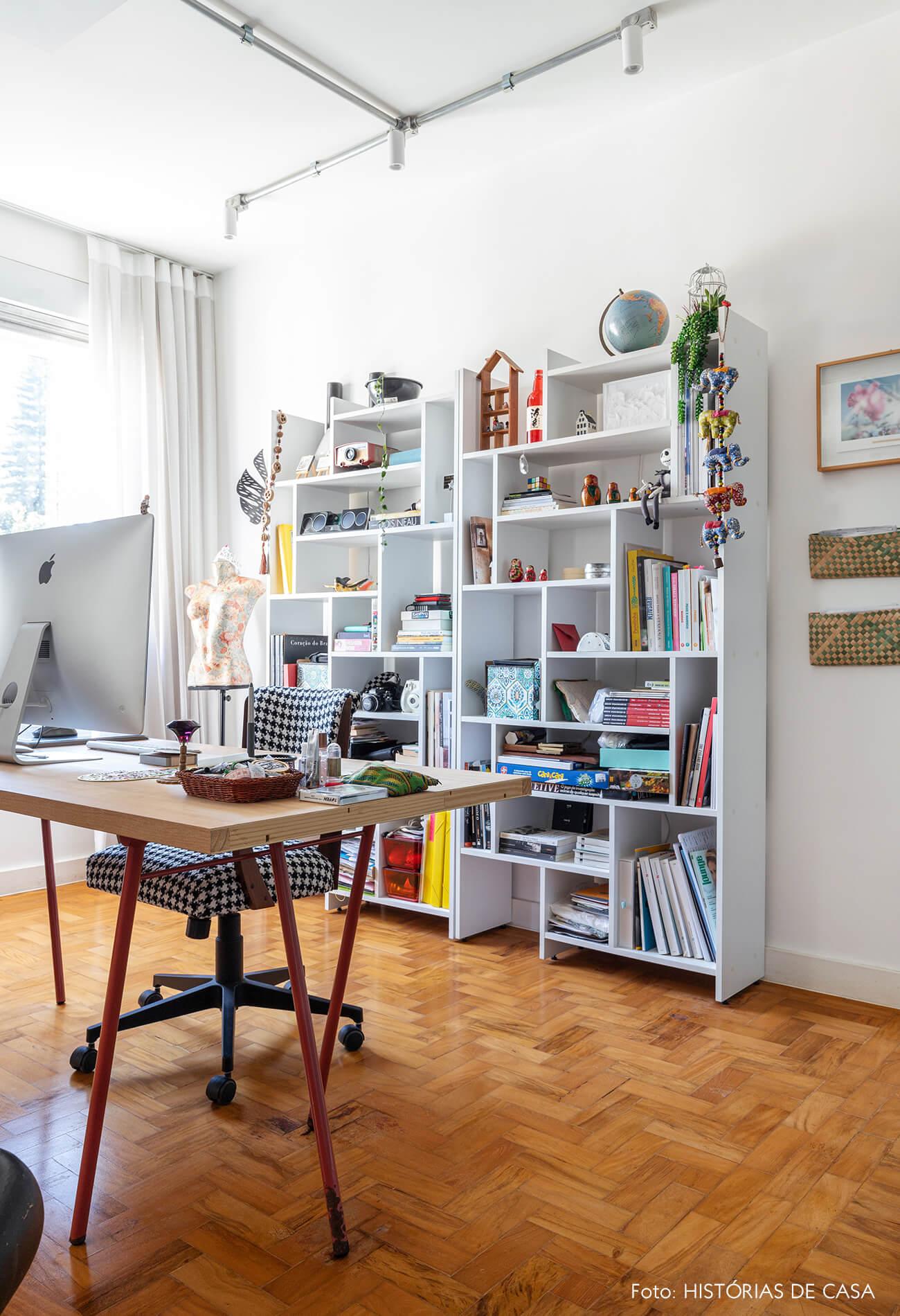 Escritório com piso de madeira e prateleira branca