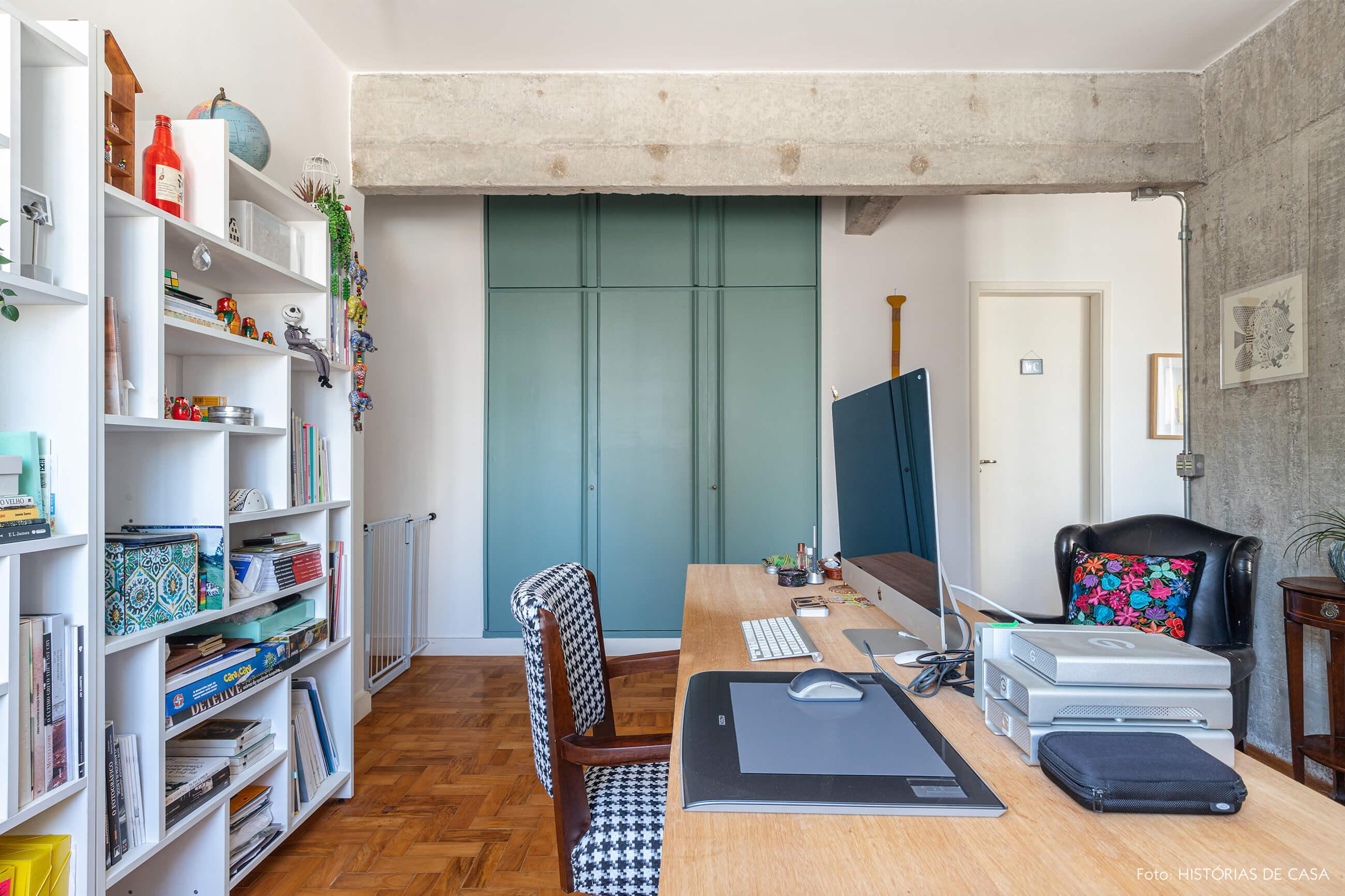 Escritório com parede de concreto e porta verde