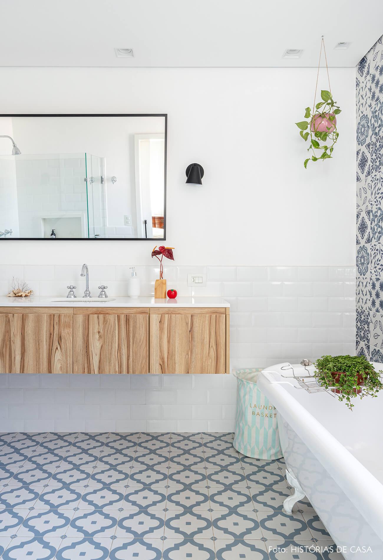 Banheiro com azulejo azul e branco banheira e plantas