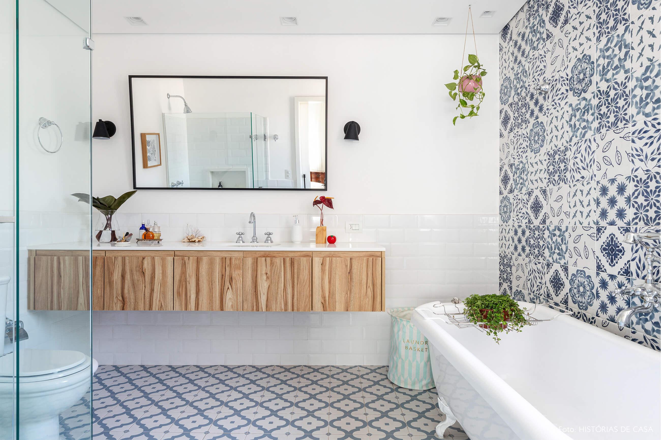 Banheiro com azulejo azul e branco e banheira e plantas