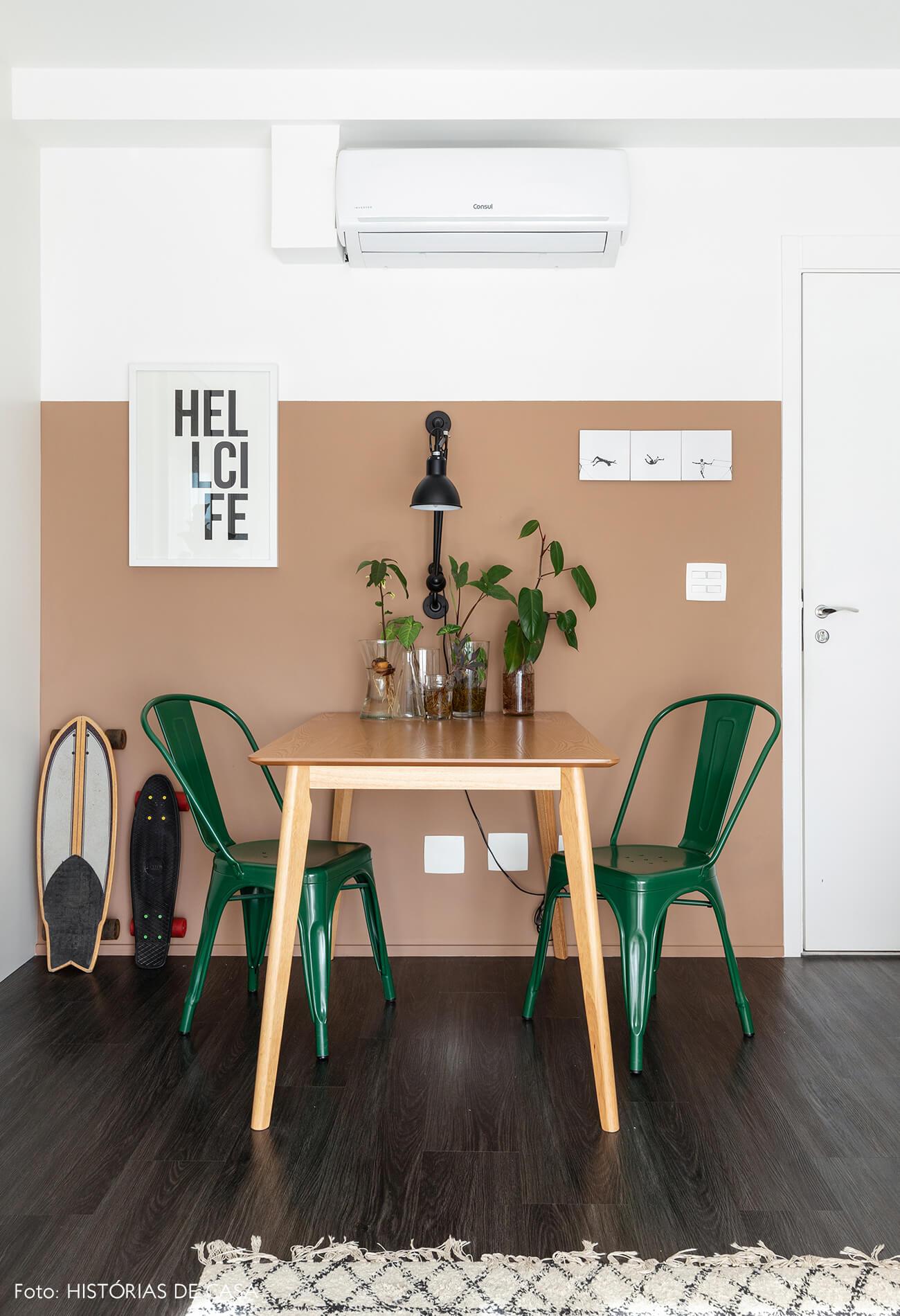 Sala com parede bege rosa e caderias verdes e piso de madeira