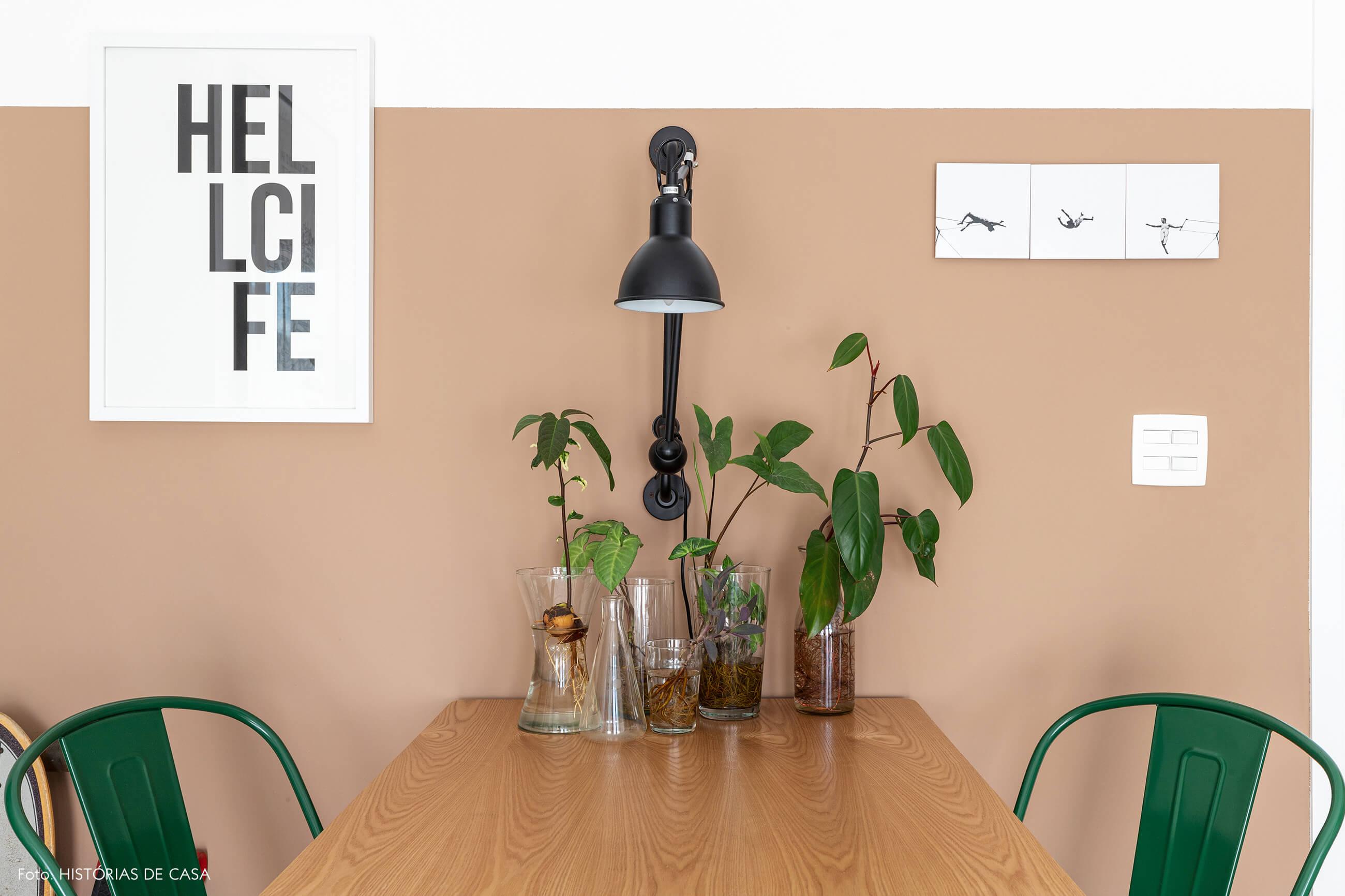 Sala com parede bege rosa e mesa de madeira clara e cadeiras verdes