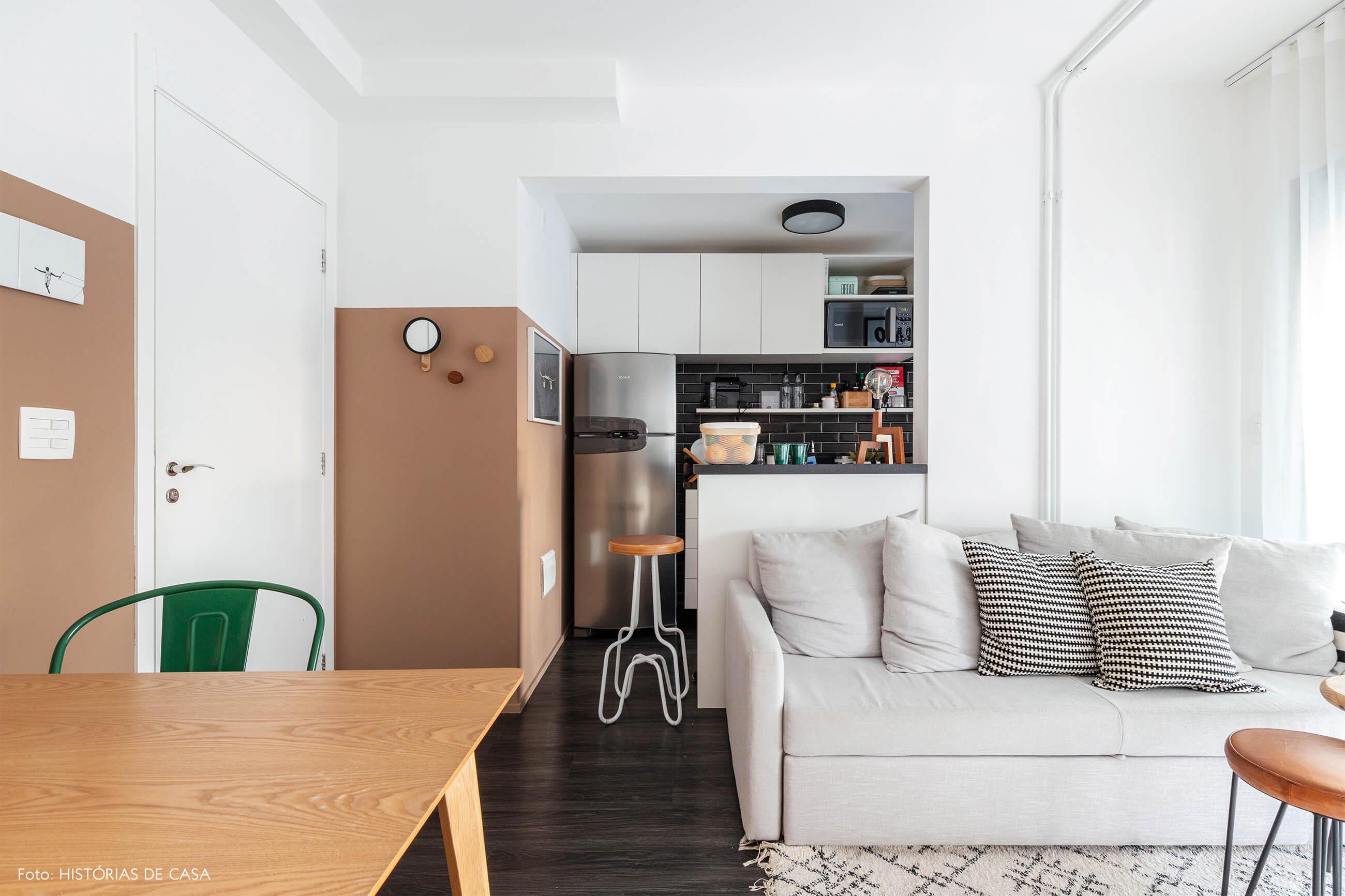 Sala e cozinha com parede bege rosa e mesa de madeira clara e sofá cinza