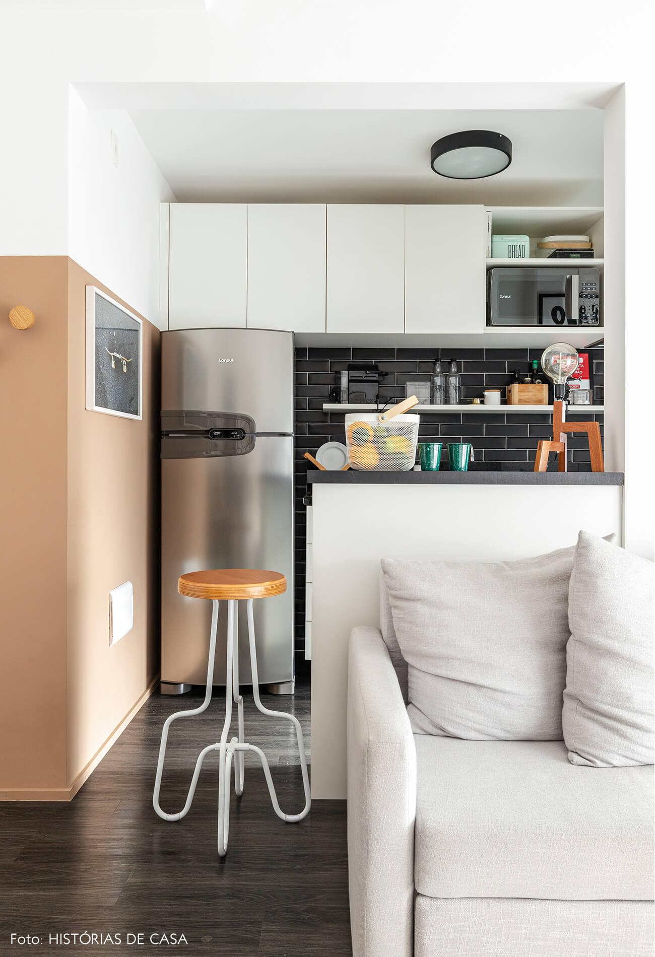 Sala cozinha com sofá cinza e piso de madeira