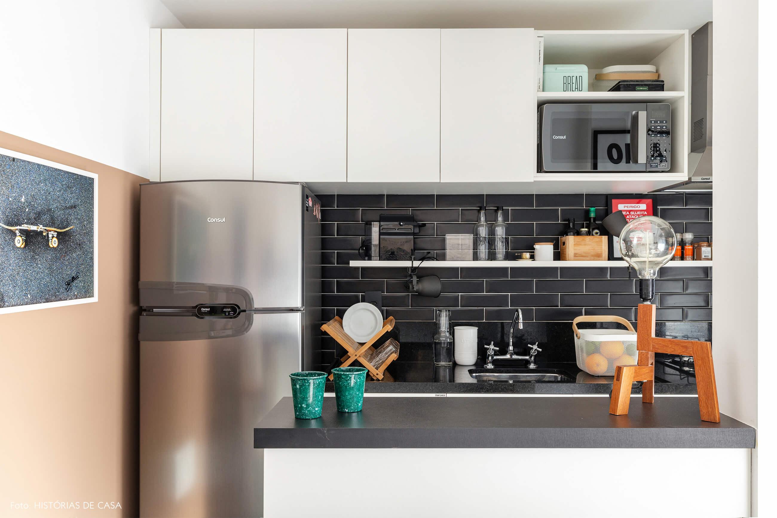 Cozinha com azulejos pretos e luminária de madeira