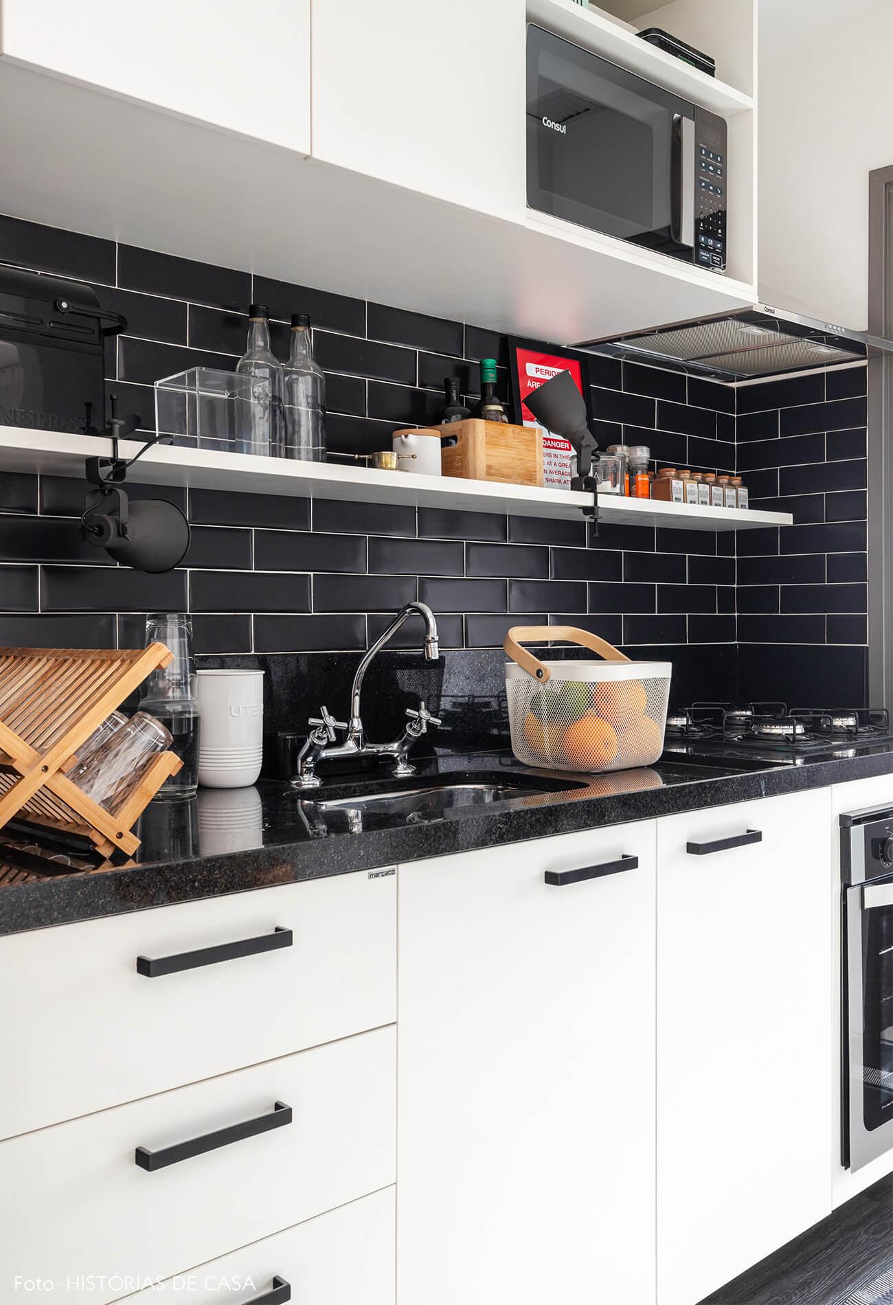 Cozinha com azulejos pretos e prateleiras brancas