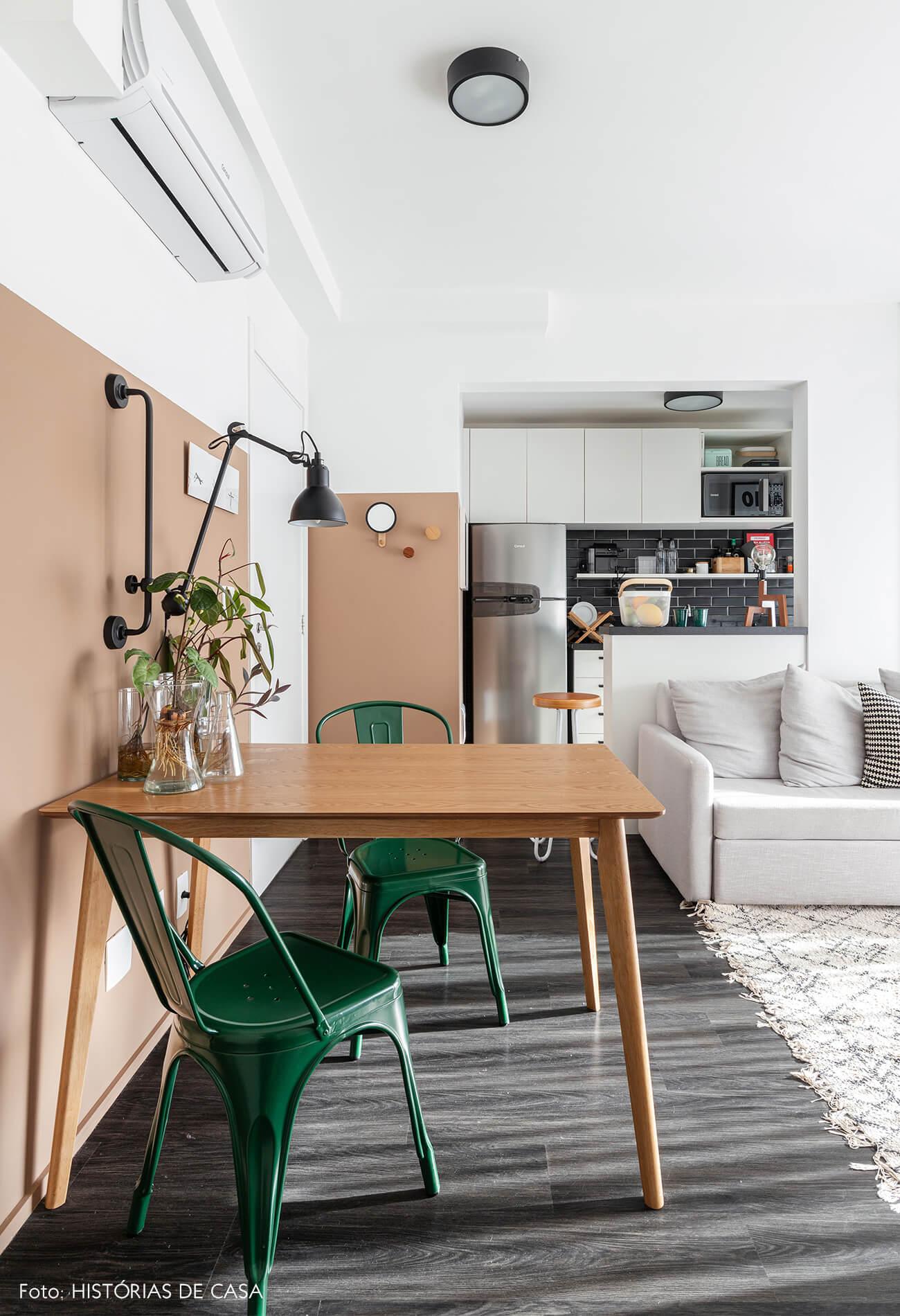 Sala cozinha com piso de madeira e parede rosa bege e cadeiras verdes