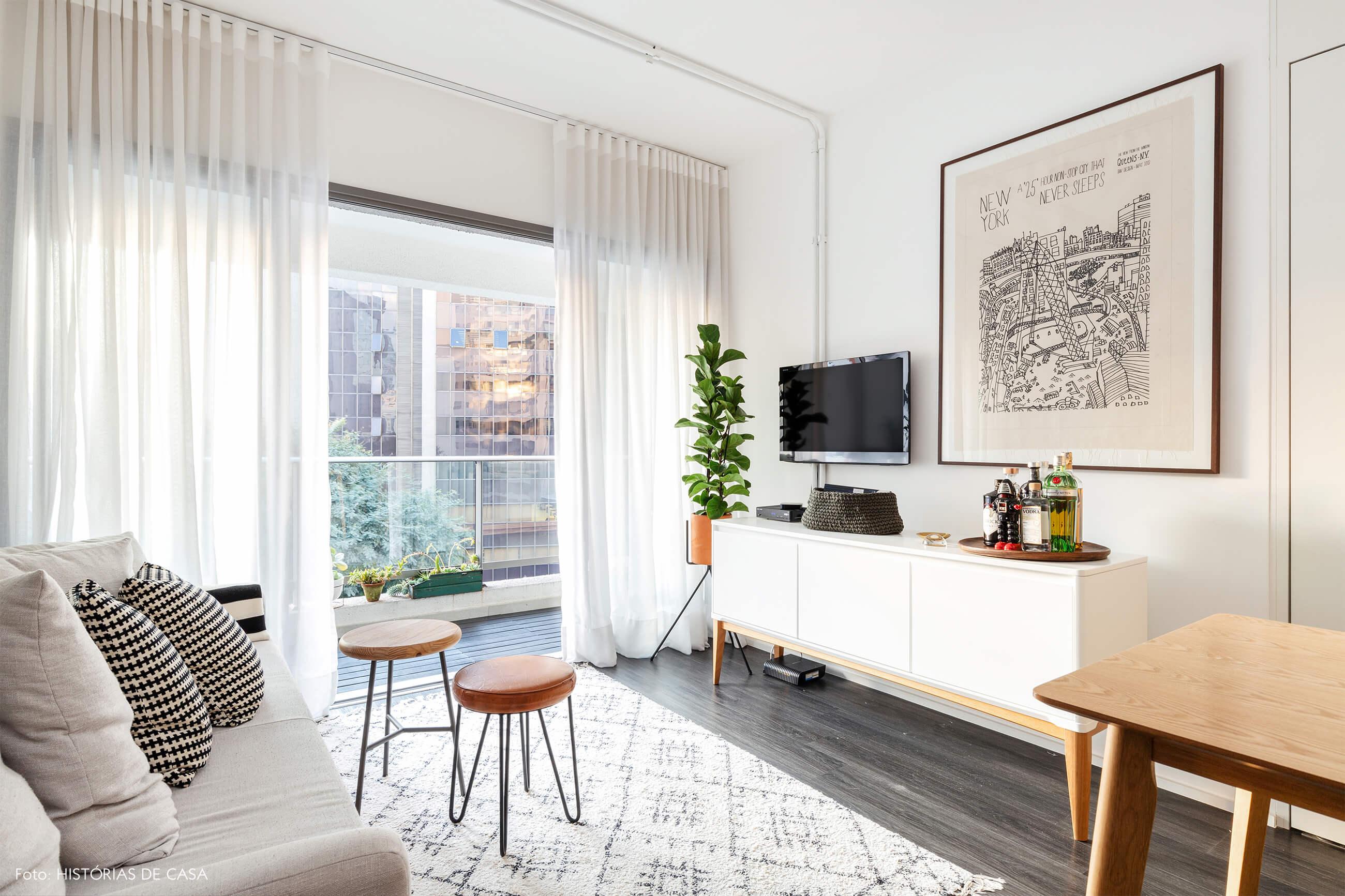 Sala com tapete branco e sofá cinza com quadro e planta
