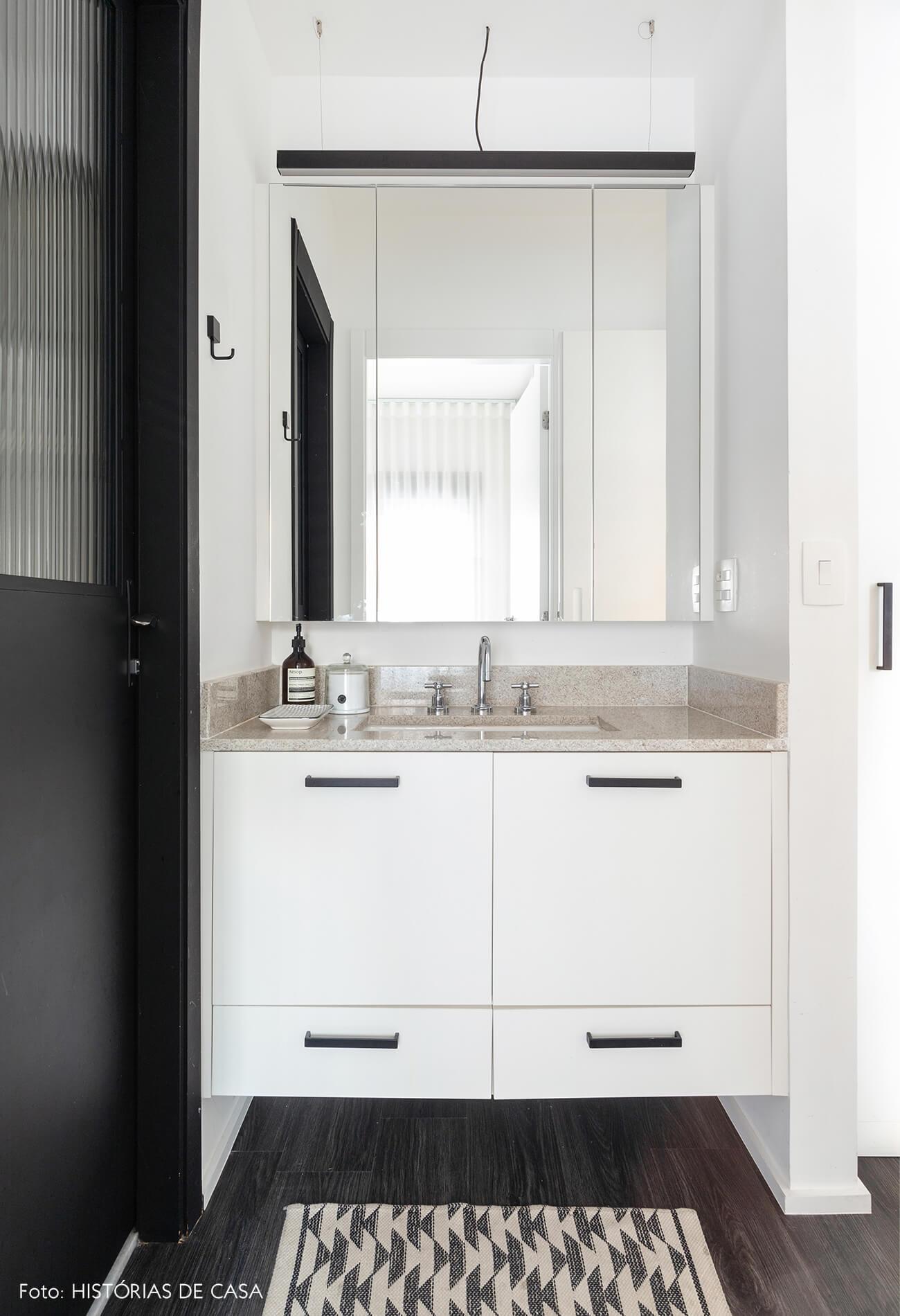 Banheir branco e porta preta com tapete estampado