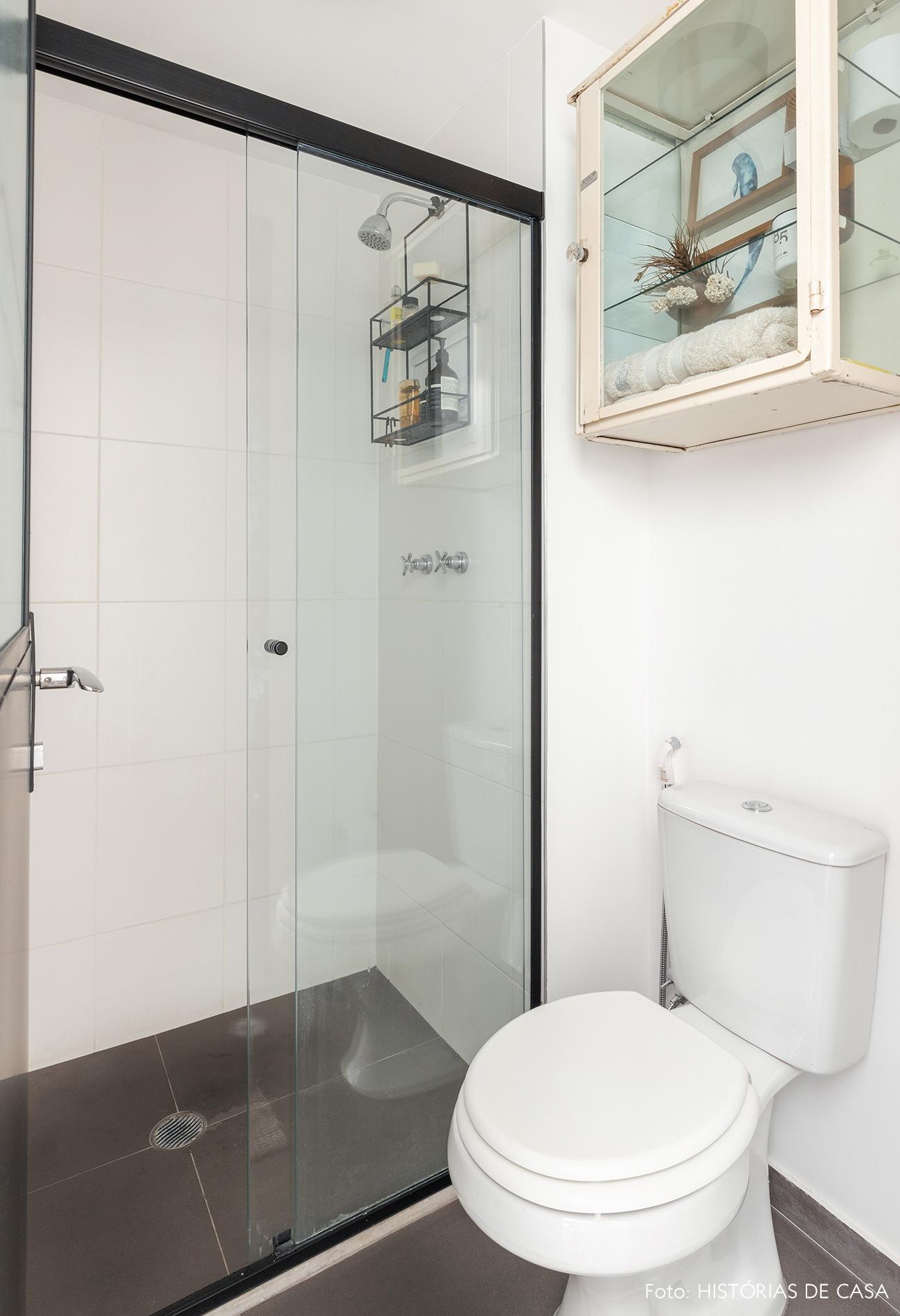 Banheiro com parede branca e piso escuro