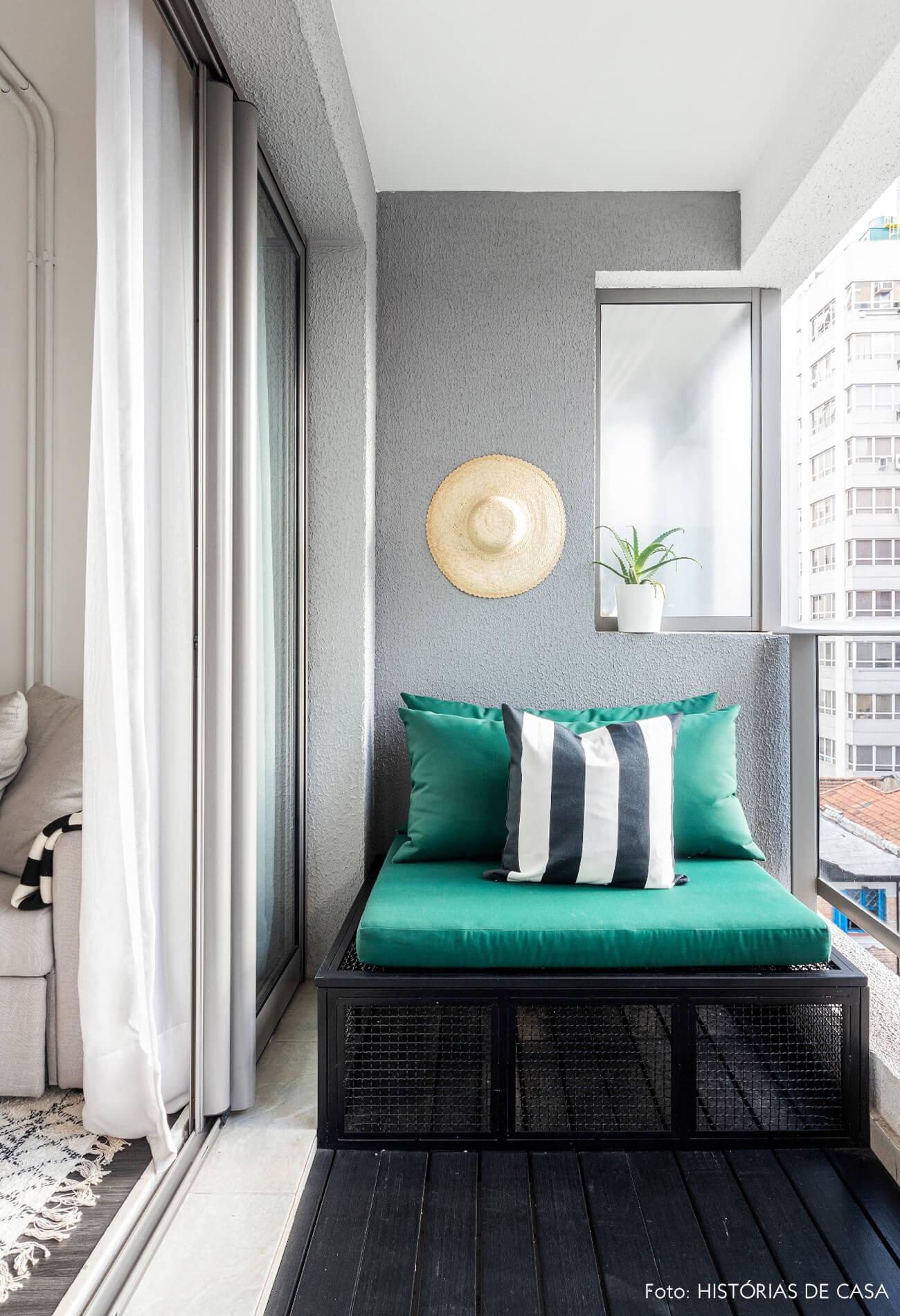 Sacada com almofadas verdes parede cinza e piso de madeira escura