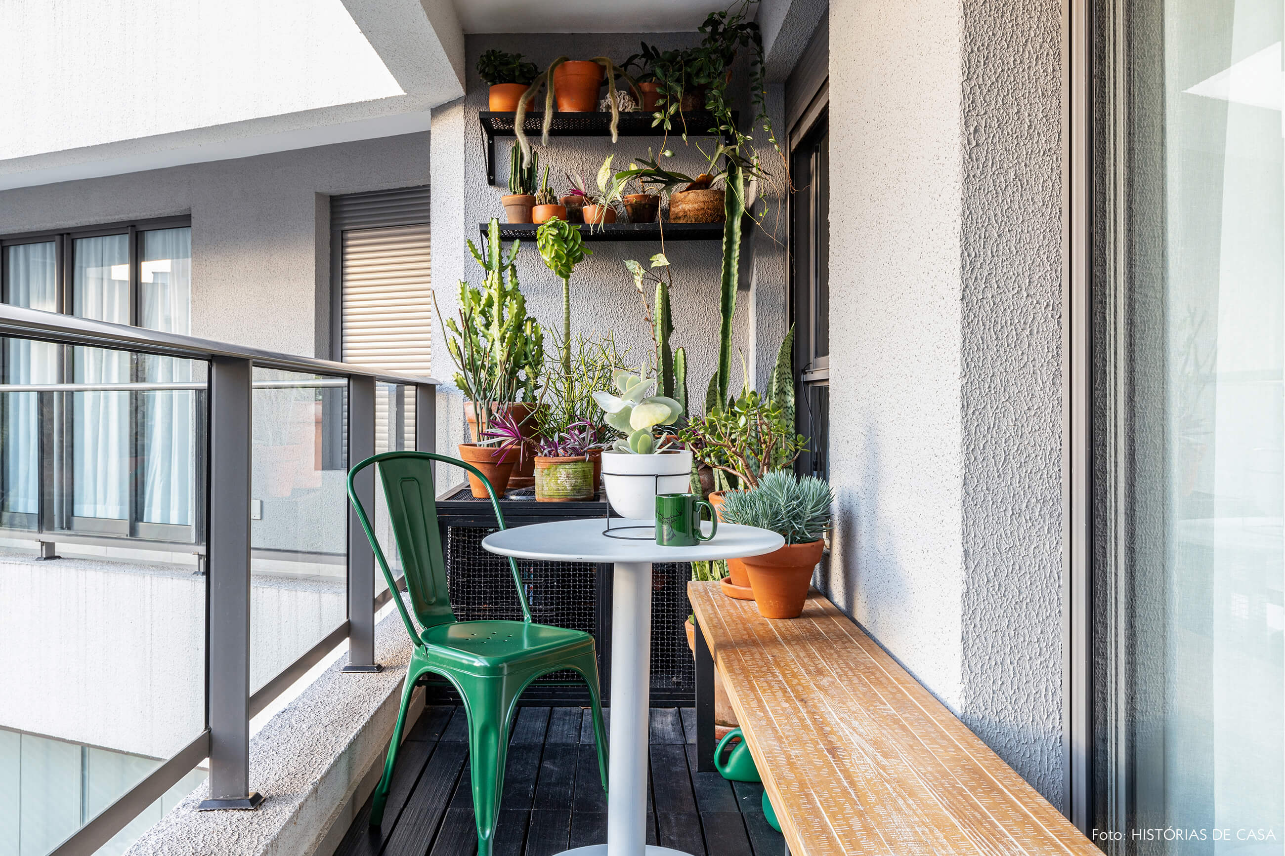 Sacada com piso de madeira escura e banco de madeira clara com cadeiras verdes e plantas