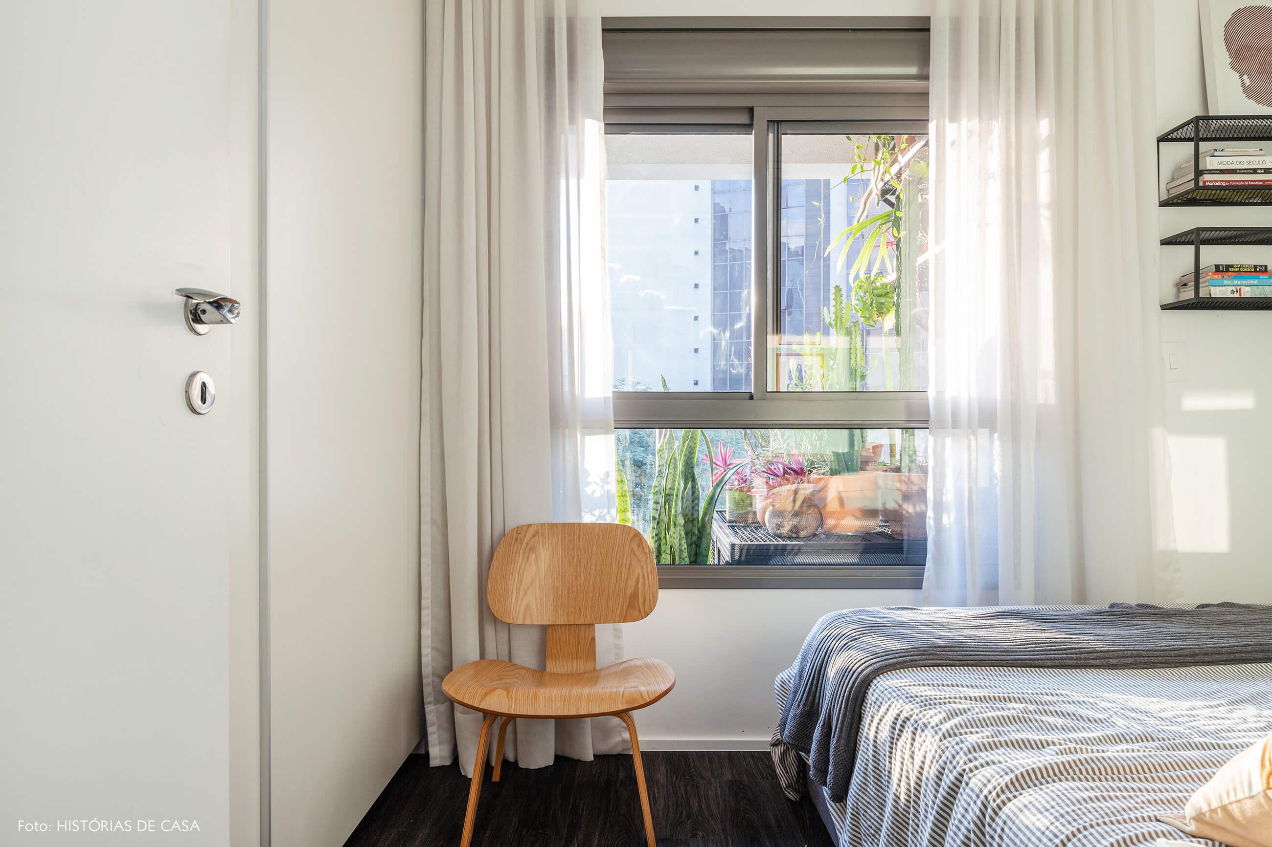 Quarto com piso escuro e paredes brancas cadeira de madeira e cama