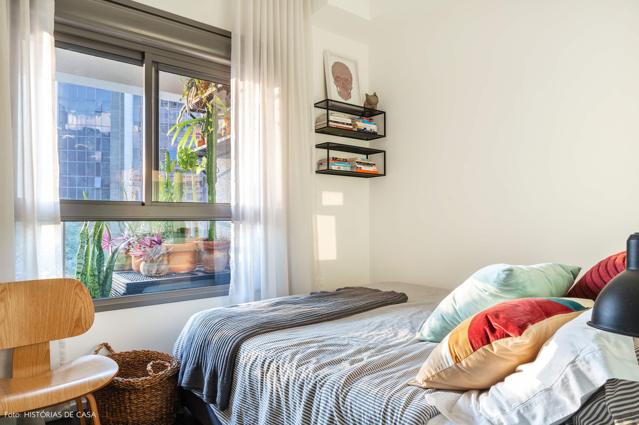 Quarto com cama com lençol listrado e almofadas coloridas