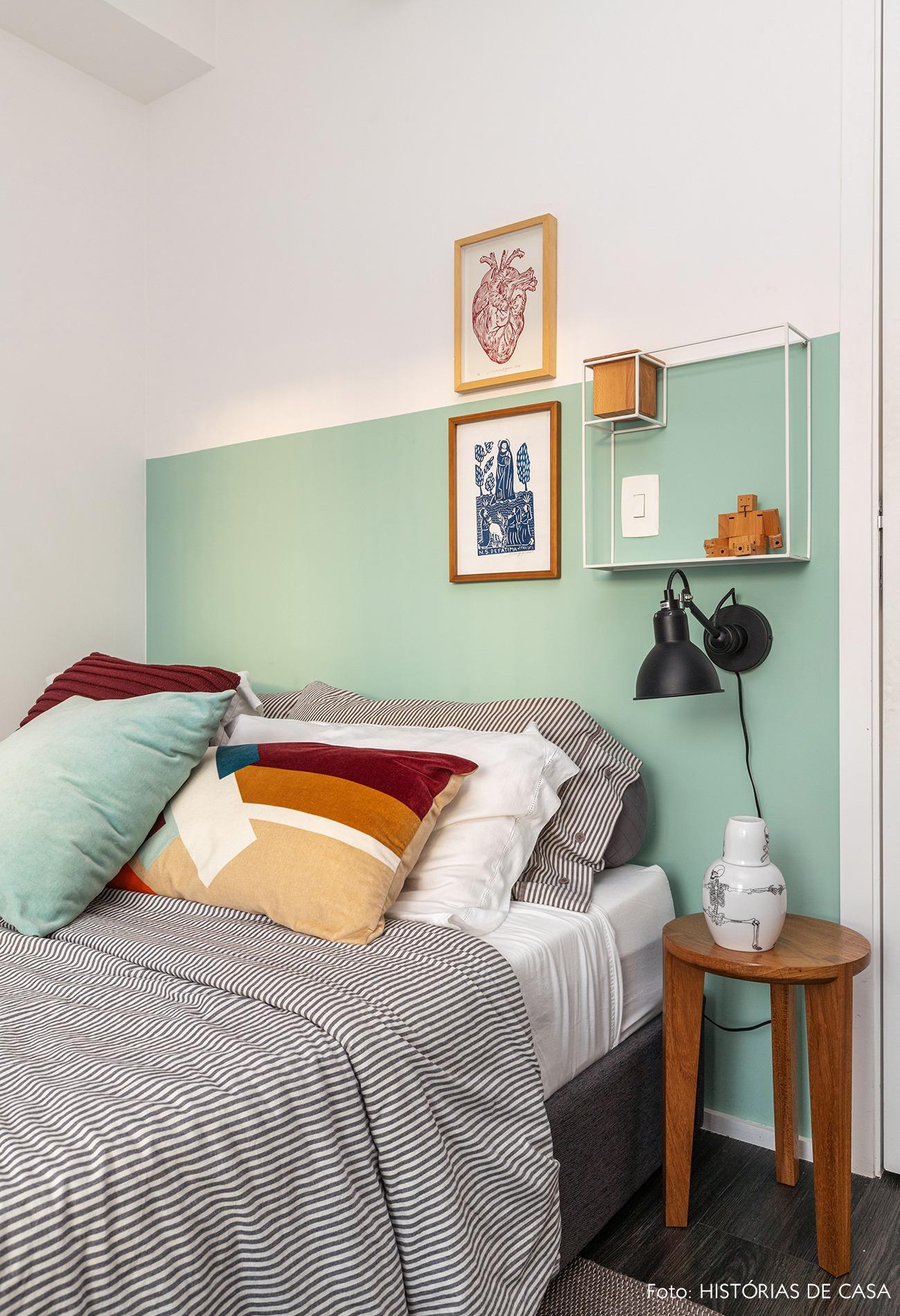 Quarto com parede verde e cama com almofadas coloridas e quadros