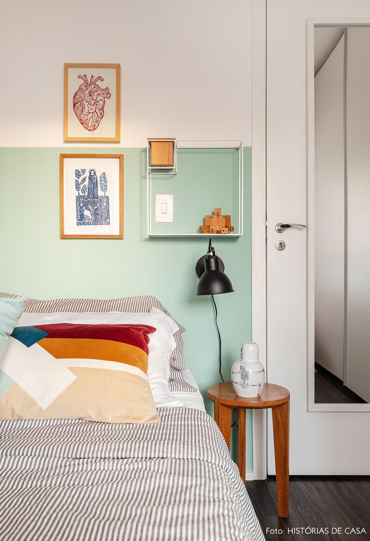 Quarto com parede verde e cama com lençol listrado e almofadas coloridas