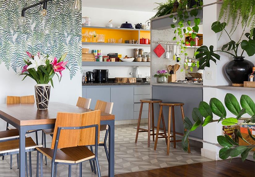 Cozinha com papel de parede estampado de plantas e cadeiras de madeira