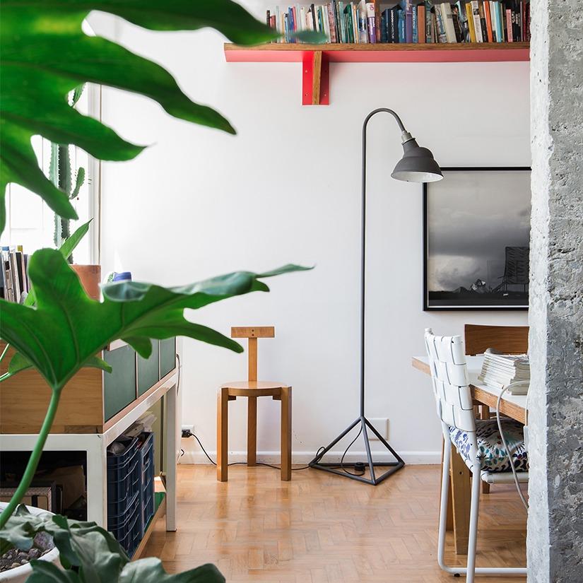 Sala com piso de madeira pilar de concreto cadeira girafa e plantas