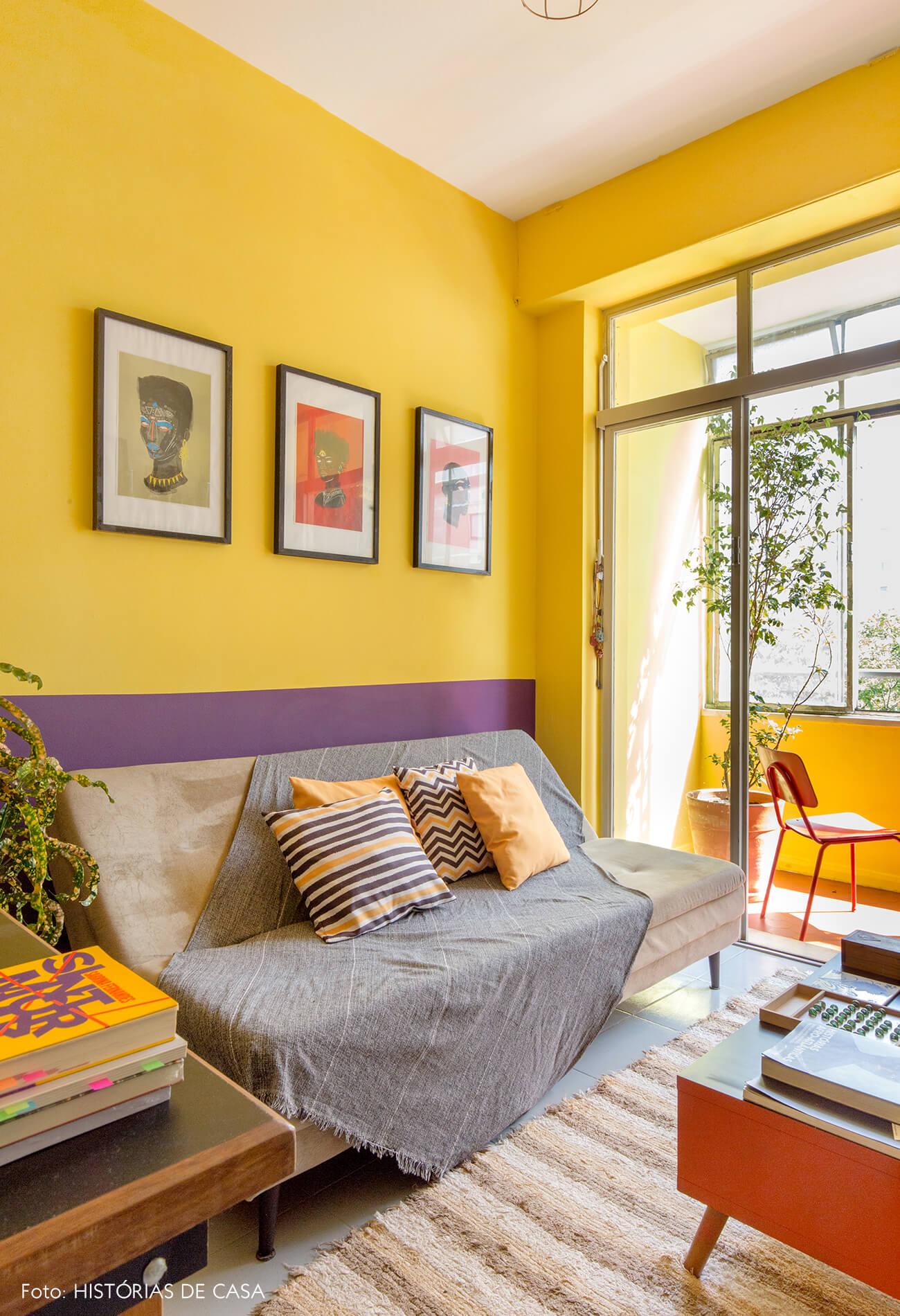 -home-office-parede-amarela-roxa-mesa-laranja-e-de-madeira-sofa-cinza-quadros-varanda
