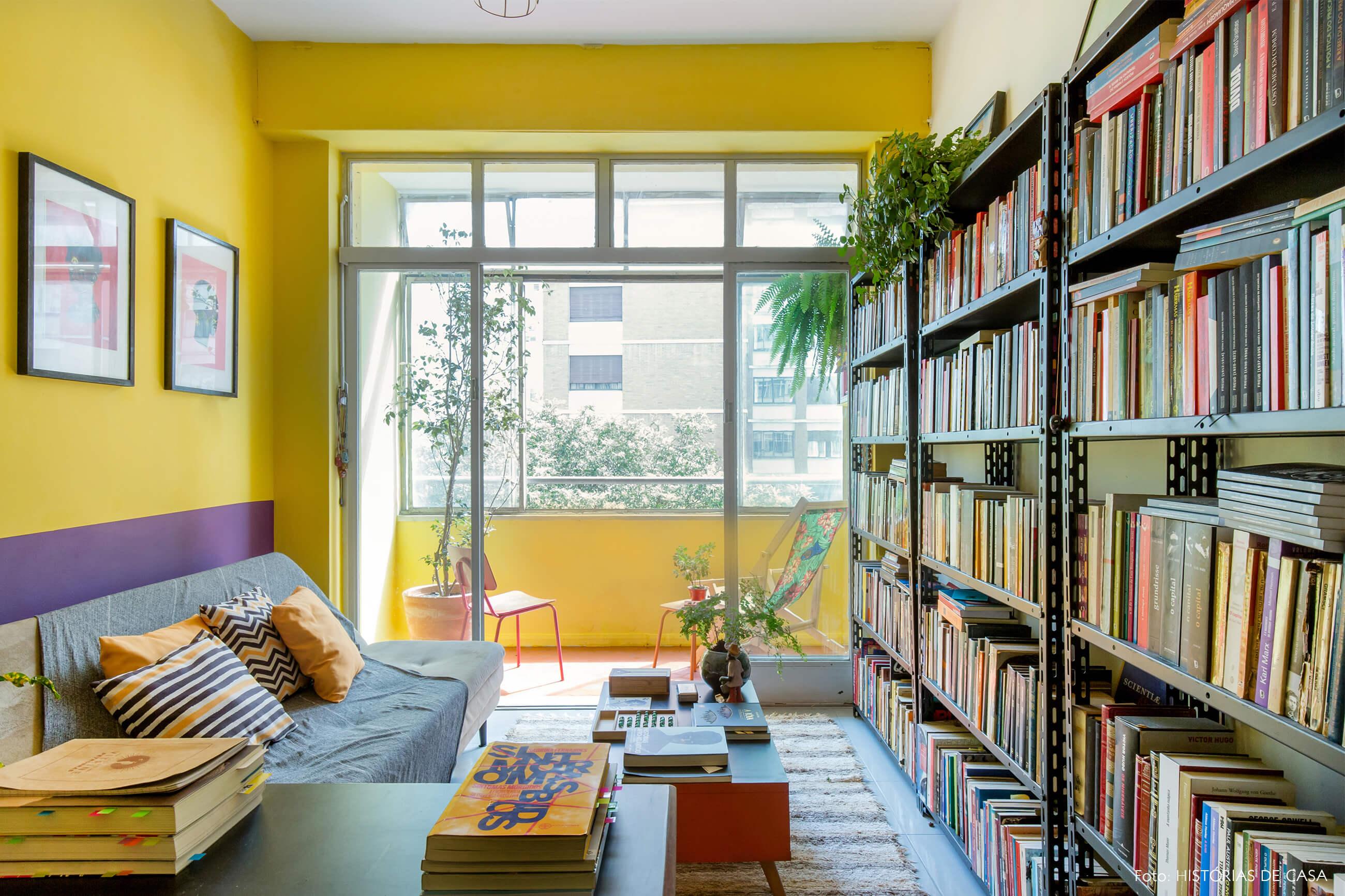 home-office-parede-amarela-e-roxa-almofadas-estampadas-amarelo-e-preto-livros-mesa-cenrto-laranja-varanda