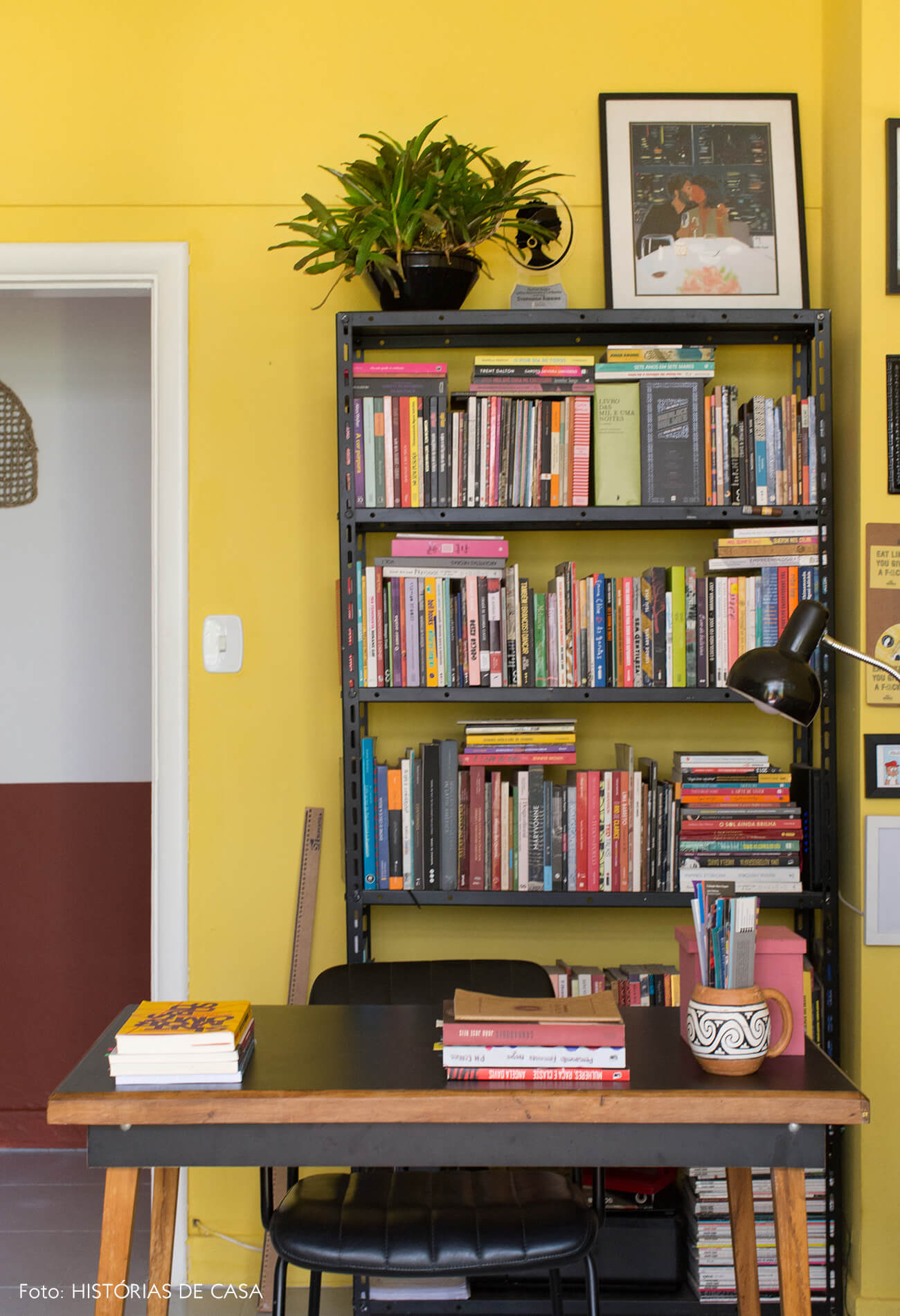 home-office-parede-amarela-mesa-madeira-preta-cadeira-preta-estante-ferro-preta