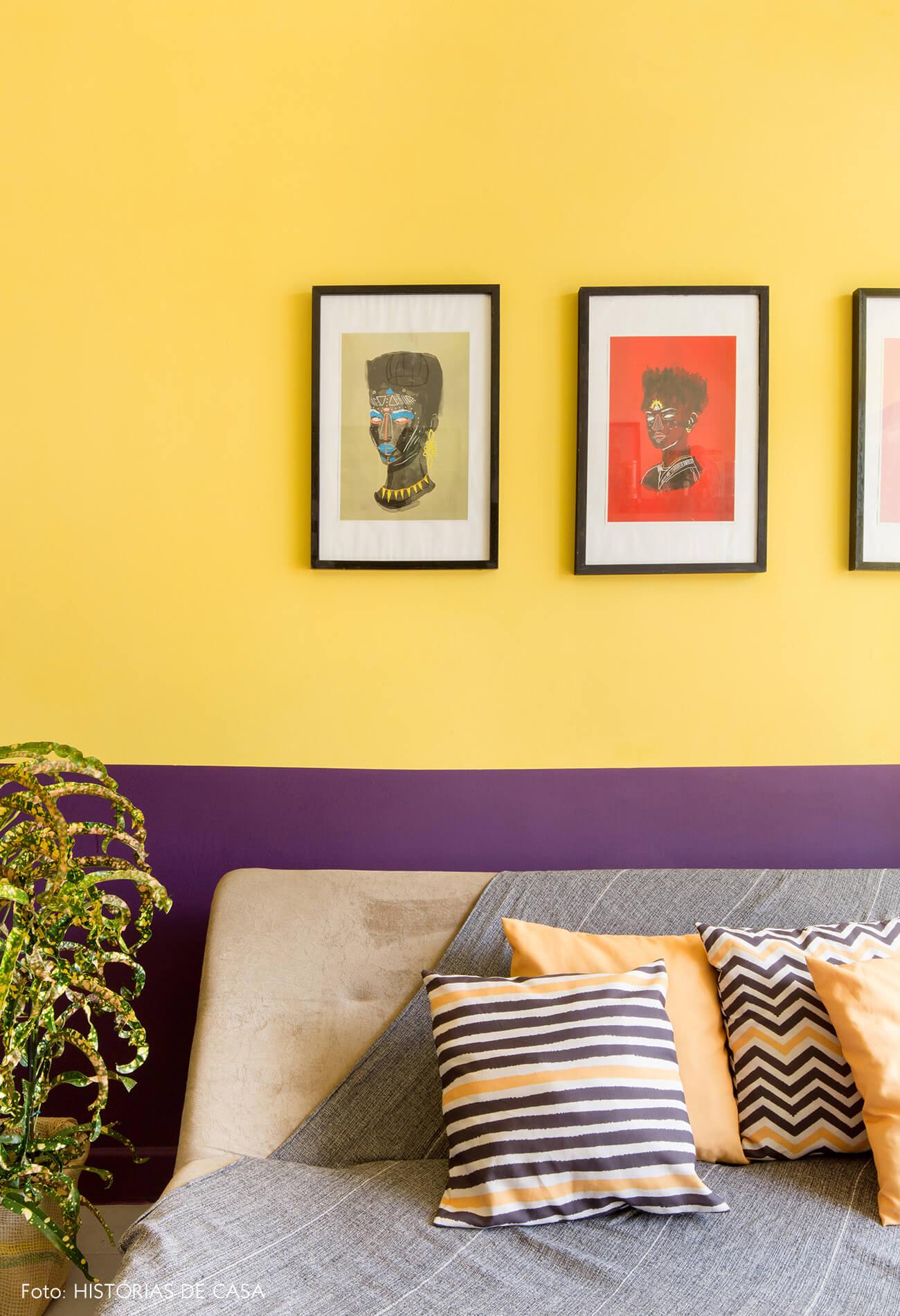 home-office-parede-amarela-e-roxa-quadros-ilustracoes-planta-almofadas-listradas-sofa-cinza
