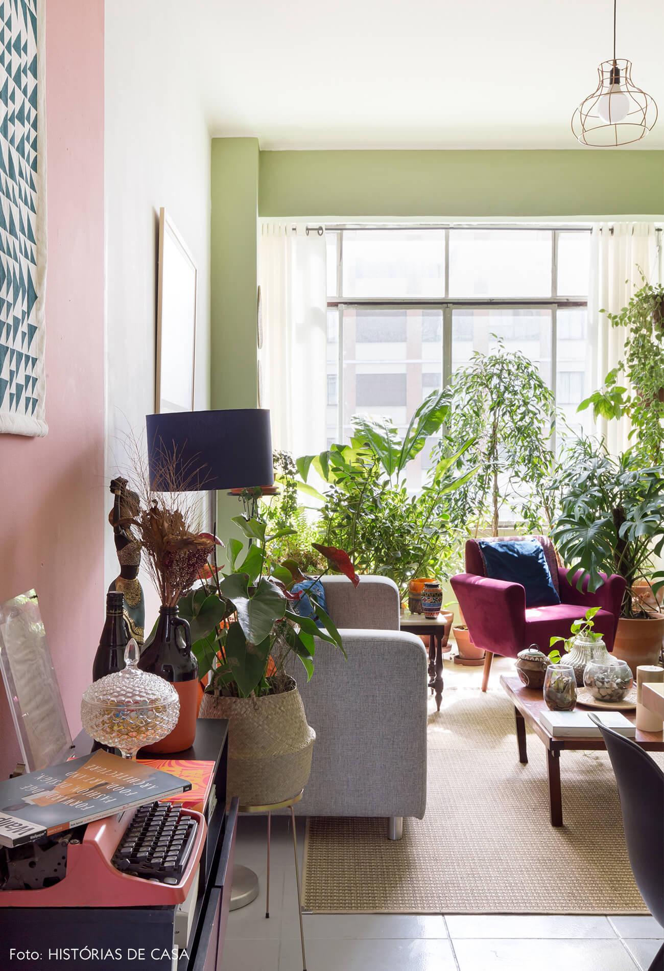 parede-rosa-e-verde-poltrona-rosa-almofada-azul-plantas-tapete-palha