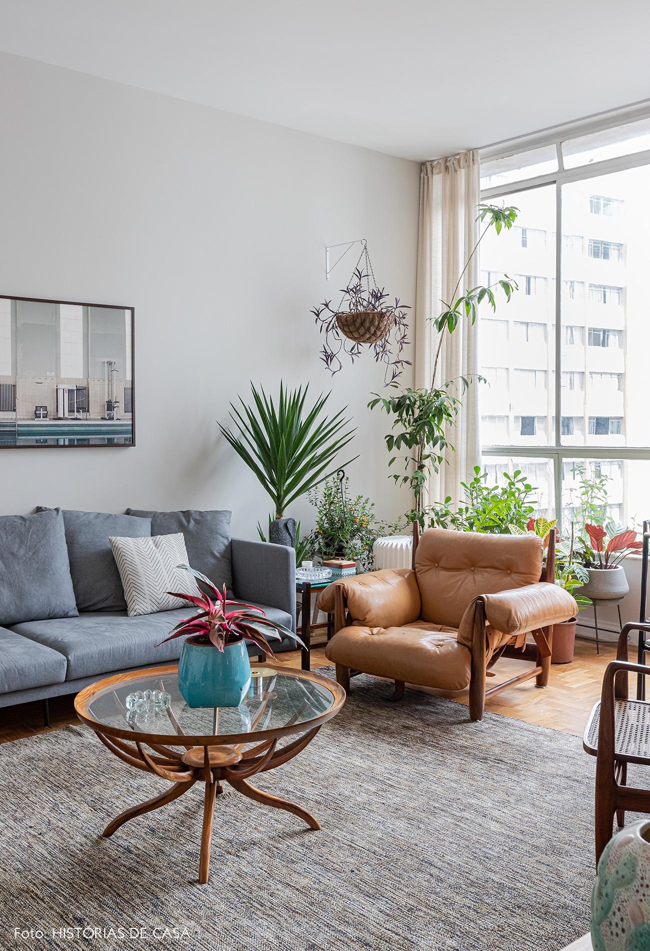 sala-poltrona-couro-tapete-sofa-cinza-mesa-madeira-vidro-redonda
