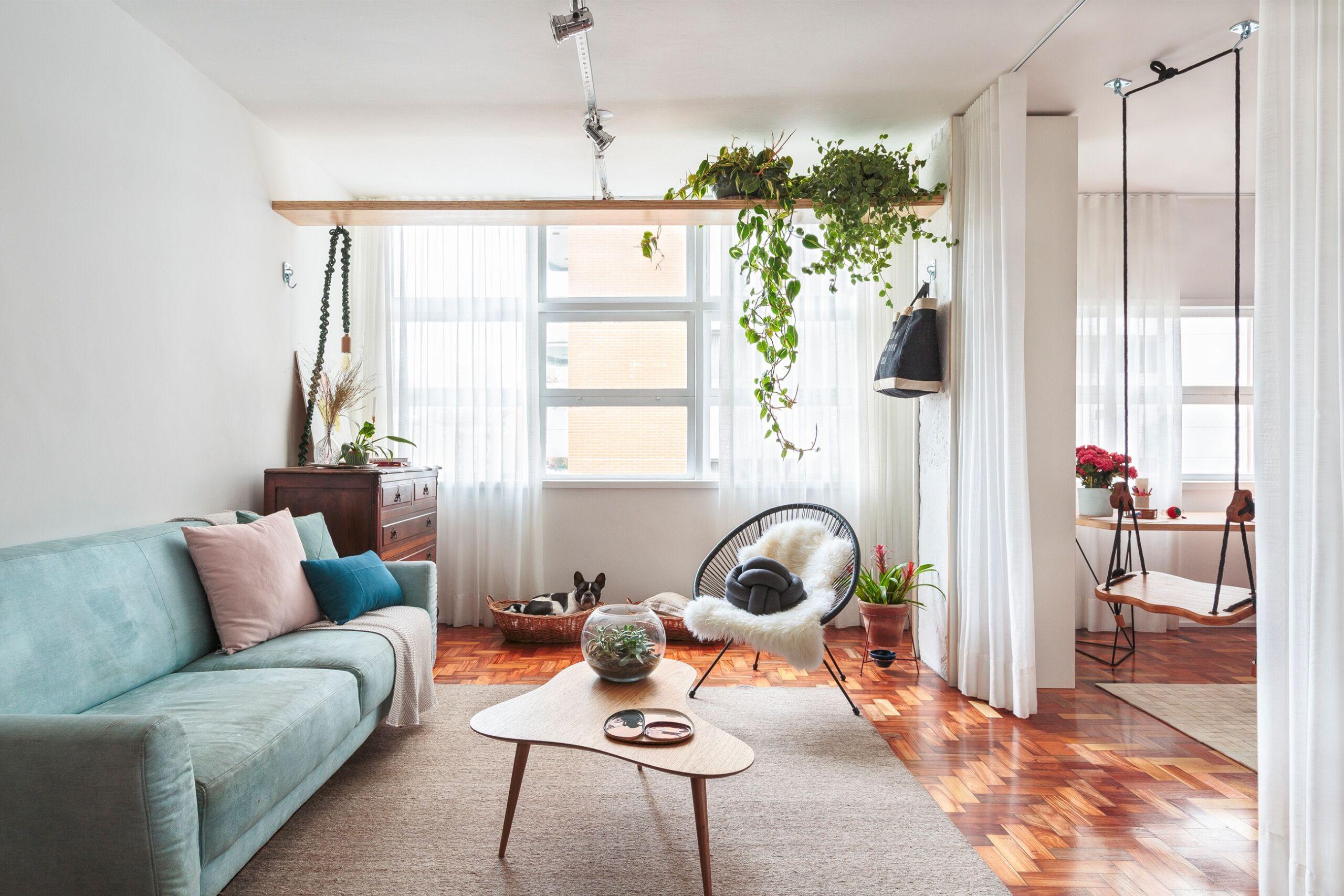 sala-mesa-curva-madeira-sofa-azul-cadeira-apulco-preta-estante-madeira-cesto-cachorro-pet-balanço