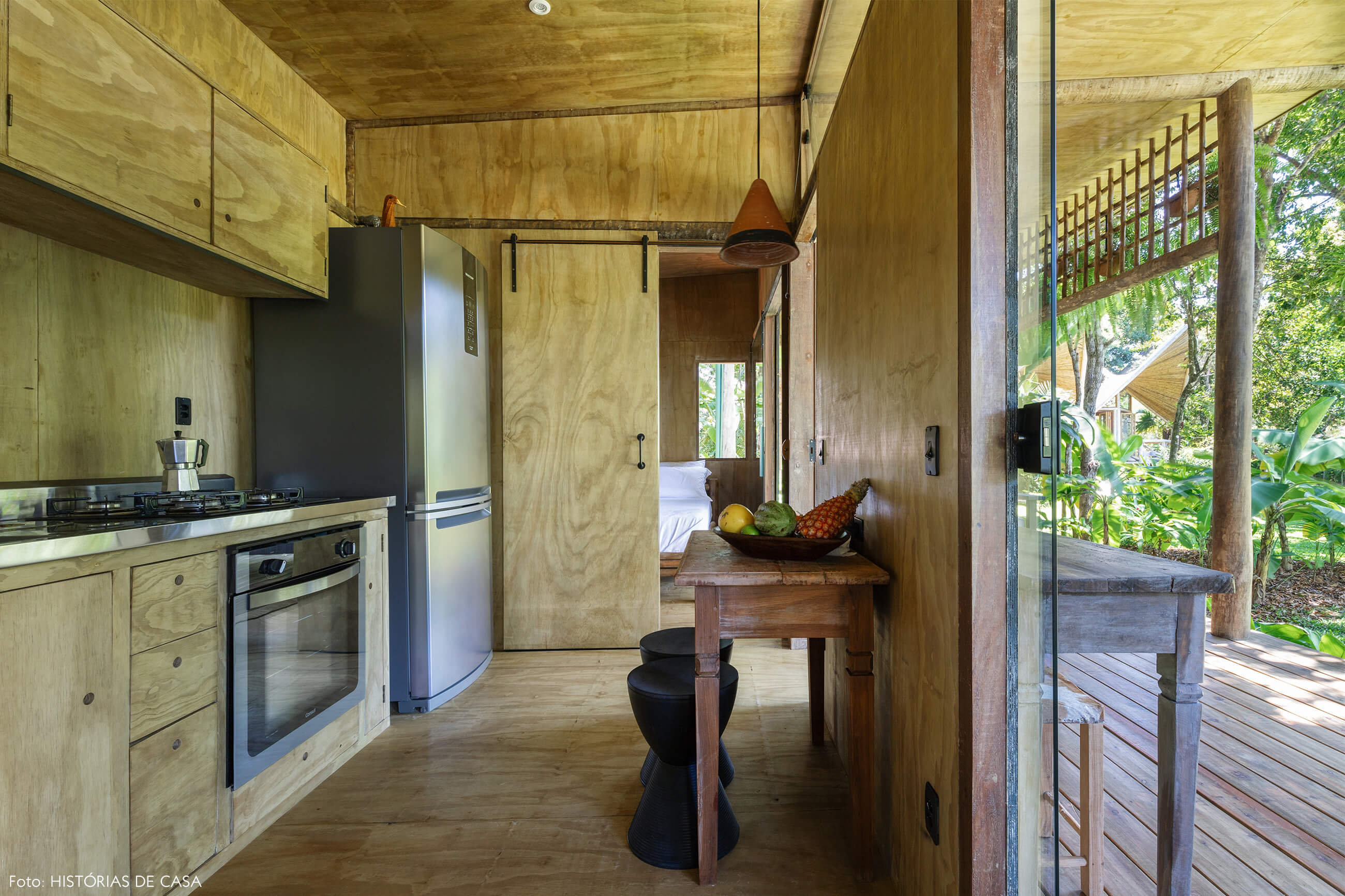 trancoso-decoracao-hotel-villase7e-27-cozinha-bancos-pretos-mesa-madeira-cafeteira-italiana-luminaria-laranja