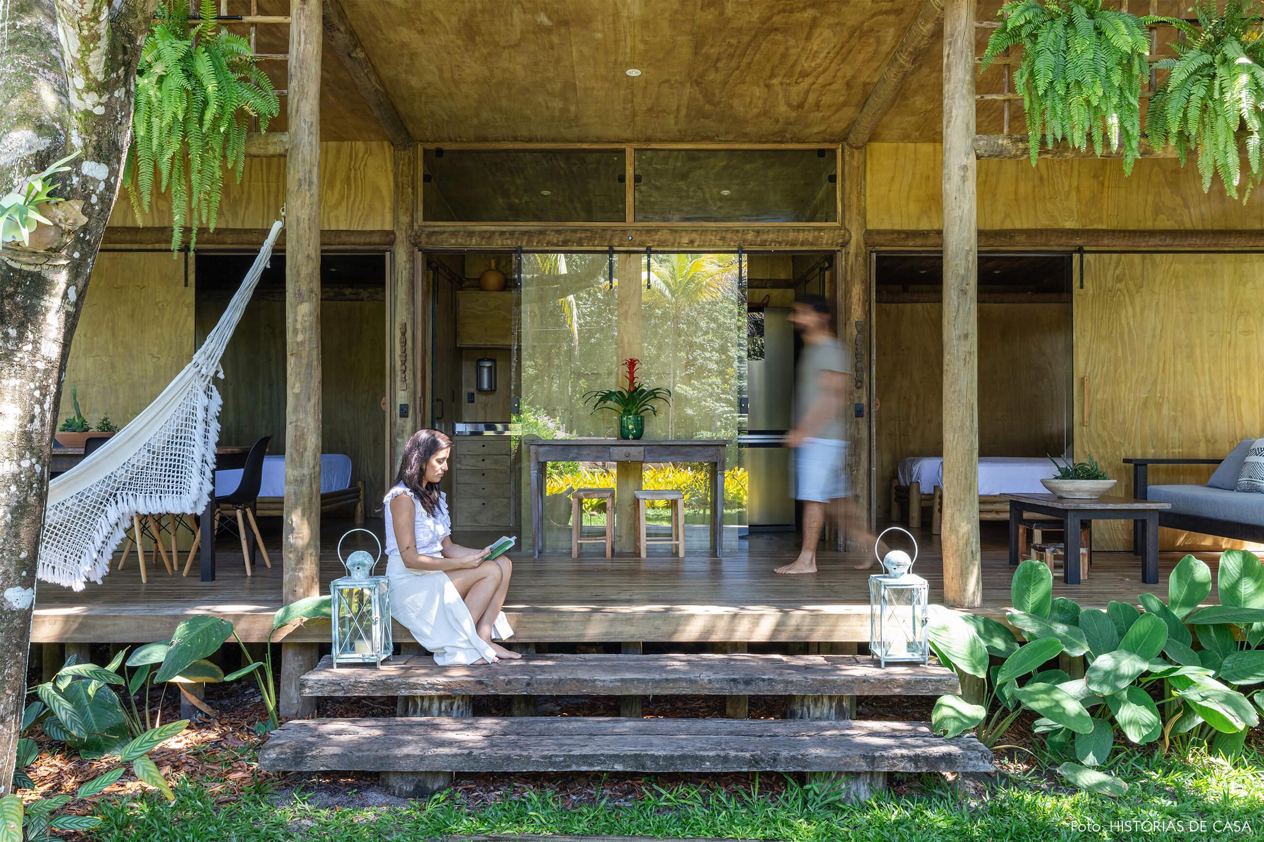 hotel-villase7e-36-retrato-entrada-madeira-rede-cadeira-eames-preta-luminaria-branca-mesa-madeira-escura-banco