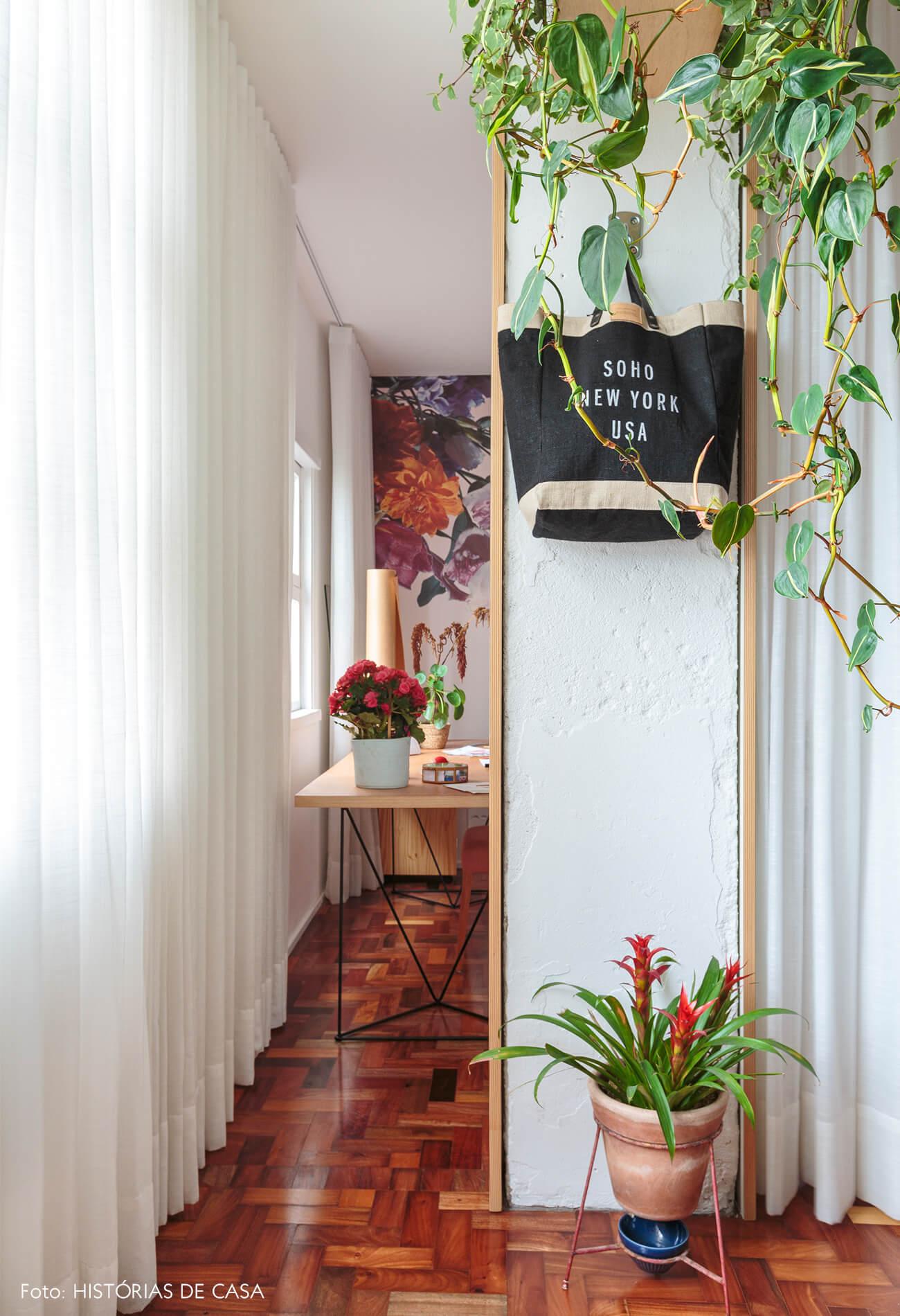 sala-home-office-atelie-parede-banca-piso-madeira-plantas-suspensas-jiboias-vaso-barro-mesa-madeira-papel-de-parede-flores-rosa